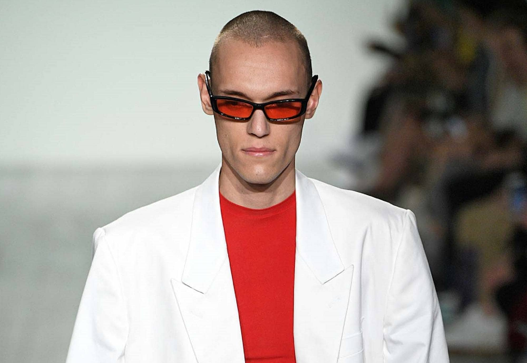 Healthy scalp: Closeup shot of a man with skinhead haircut wearing a white suit on the runway