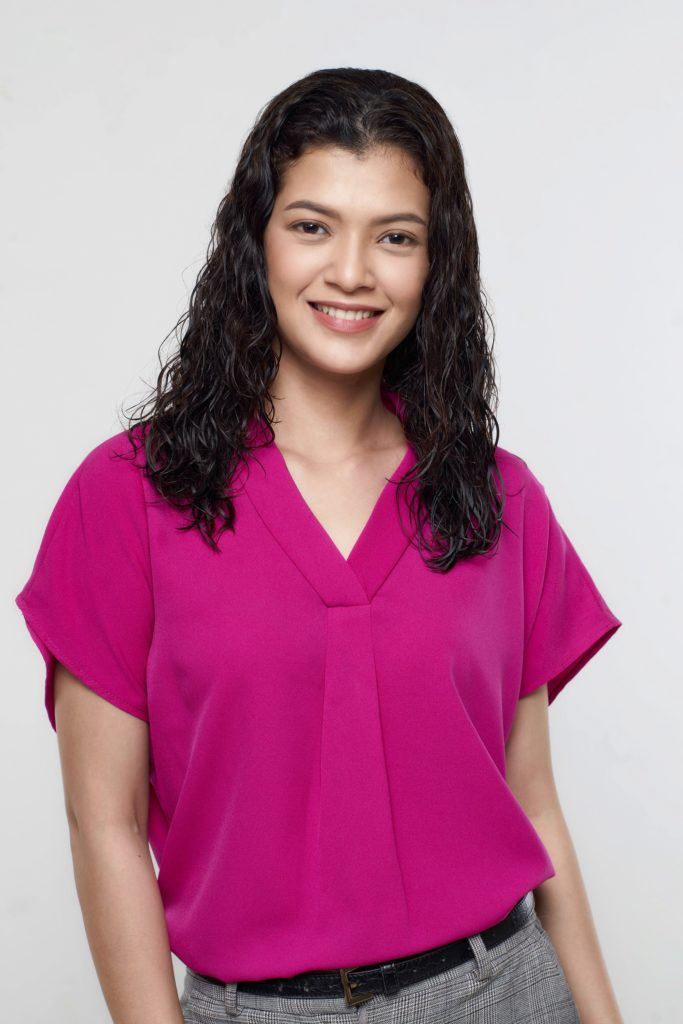 How to brush curly hair: Asian woman with dark shoulder length curly hair wearing a pink blouse