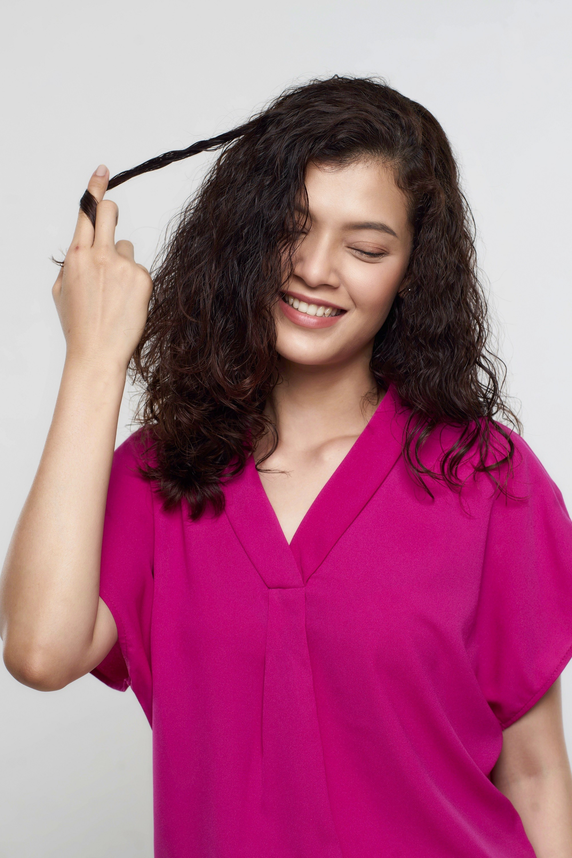 How to brush curly hair: Asian woman twirling a section of her dark curly hair