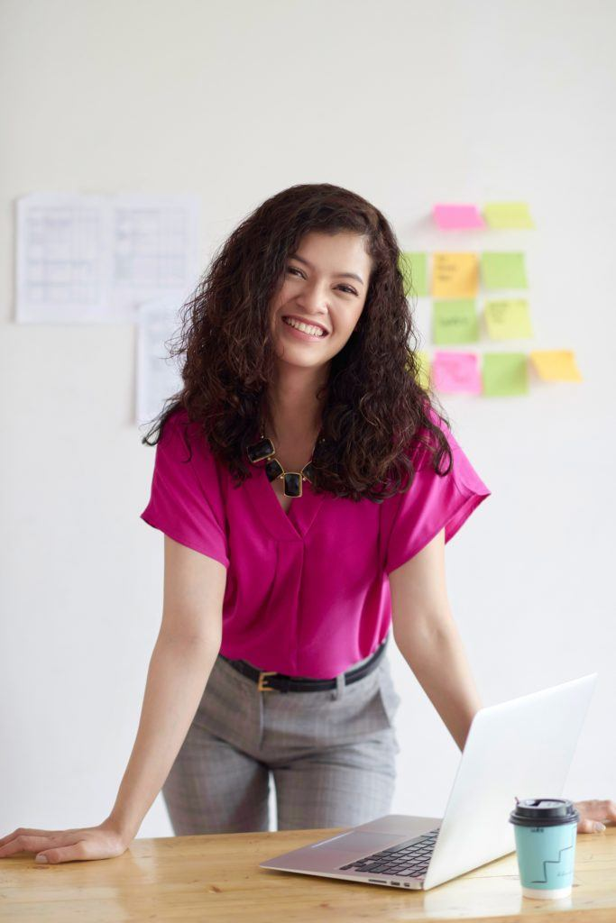How to brush curly hair: Asian woman with dark curly hair wearing a fuchsia blouse standing behind a work desk