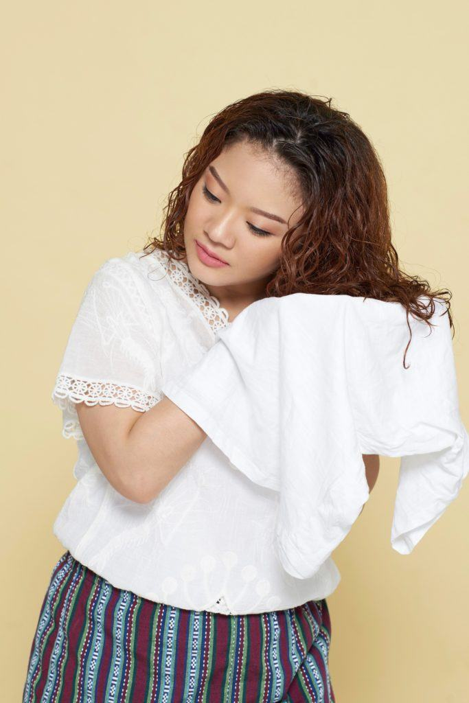 How to style curly hair: Asian woman drying her long brown curly hair with a white shirt