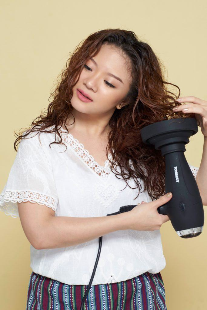 How to style curly hair: Asian woman using a diffuser on her long brown curly hair
