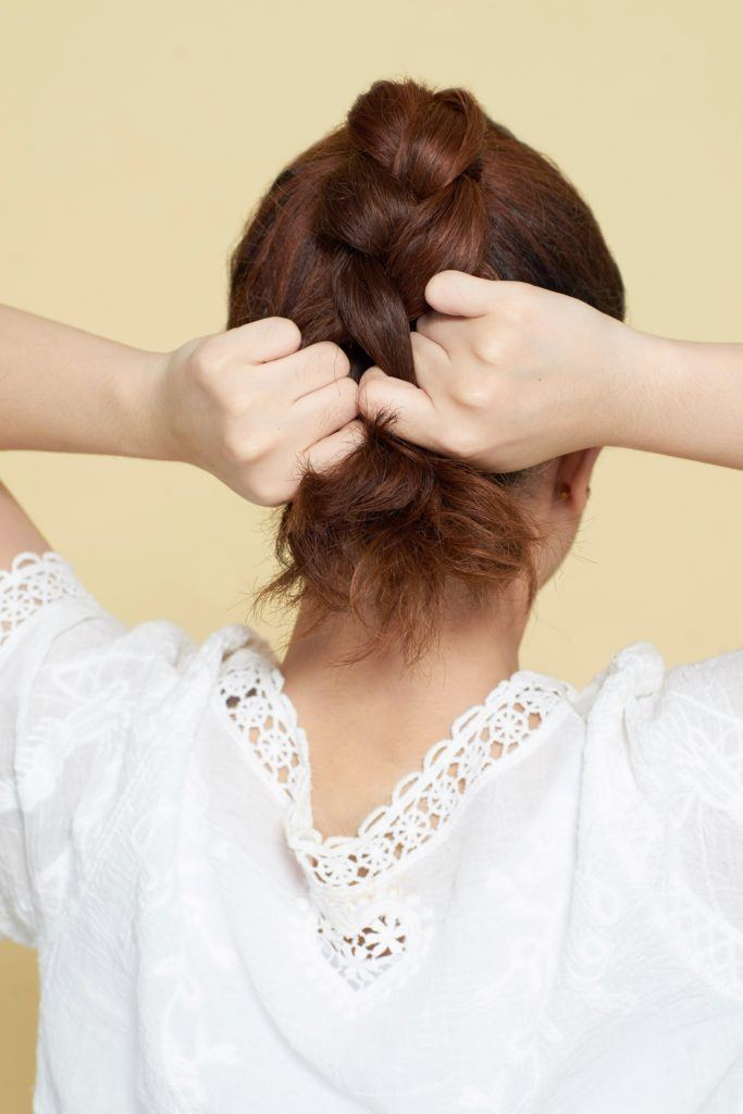 How to style curly hair: Back shot of an Asian woman braiding her long brown curly hair