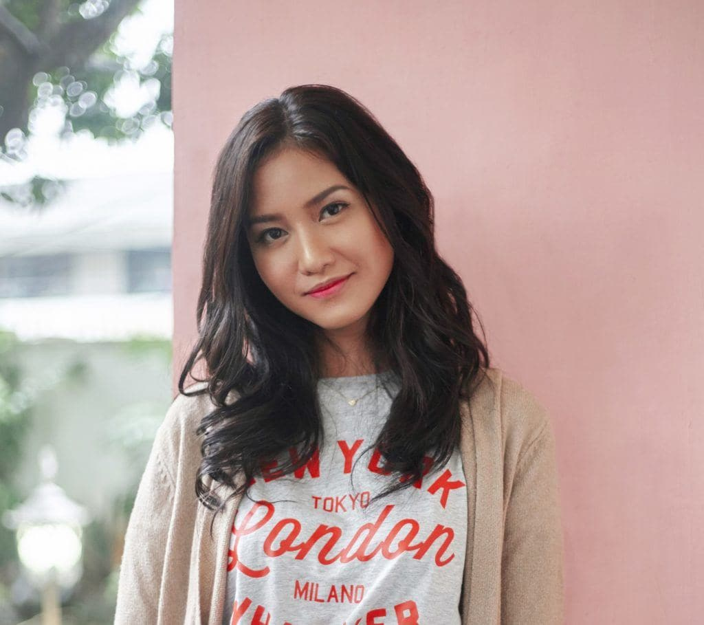 Hair types: Asian woman with long black wavy hair wearing a shirt and cardigan against a pink wall outdoors