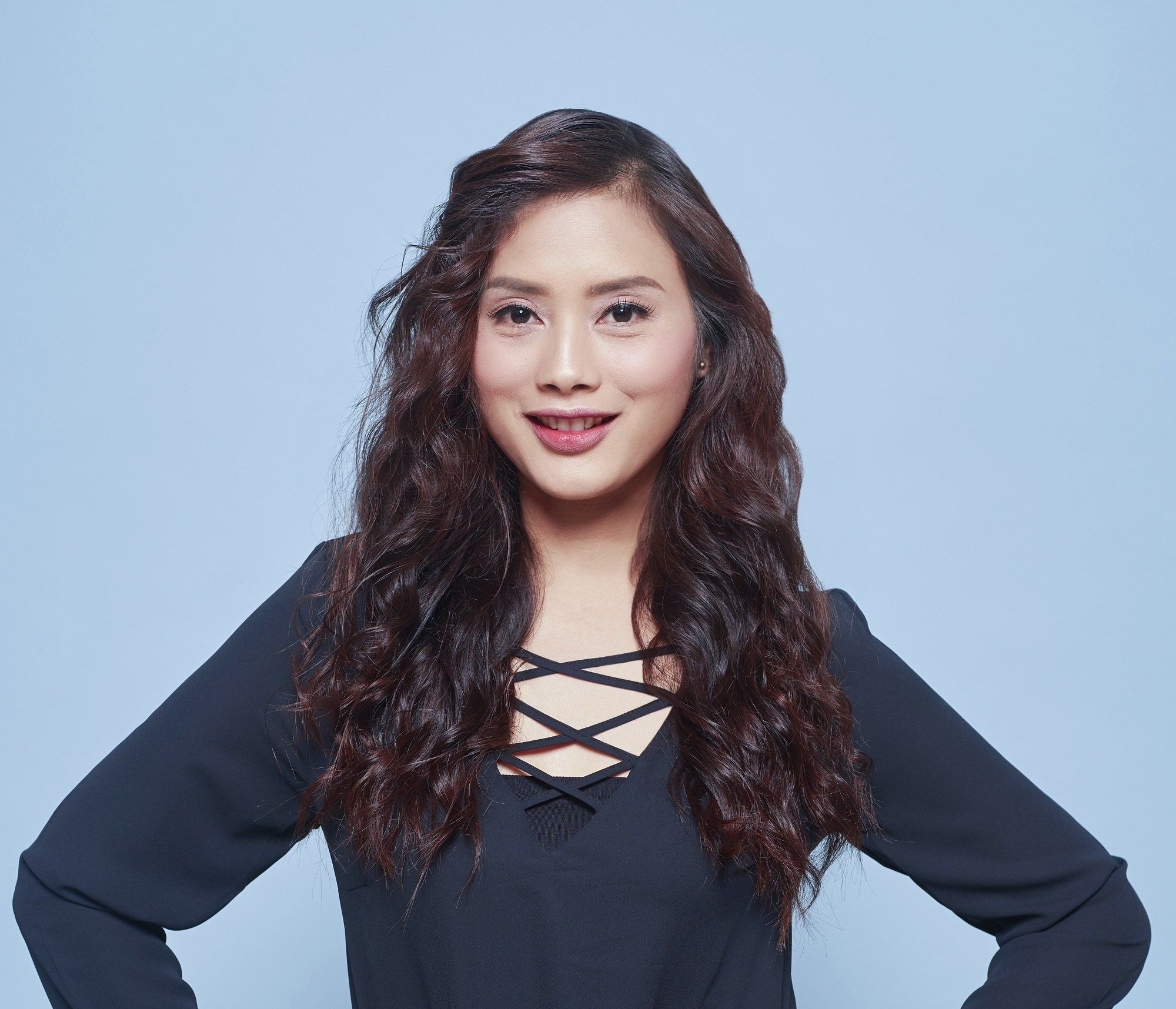 Long wavy hair: Asian woman with long dark wavy hair wearing dark blue long sleeves against a blue backdrop