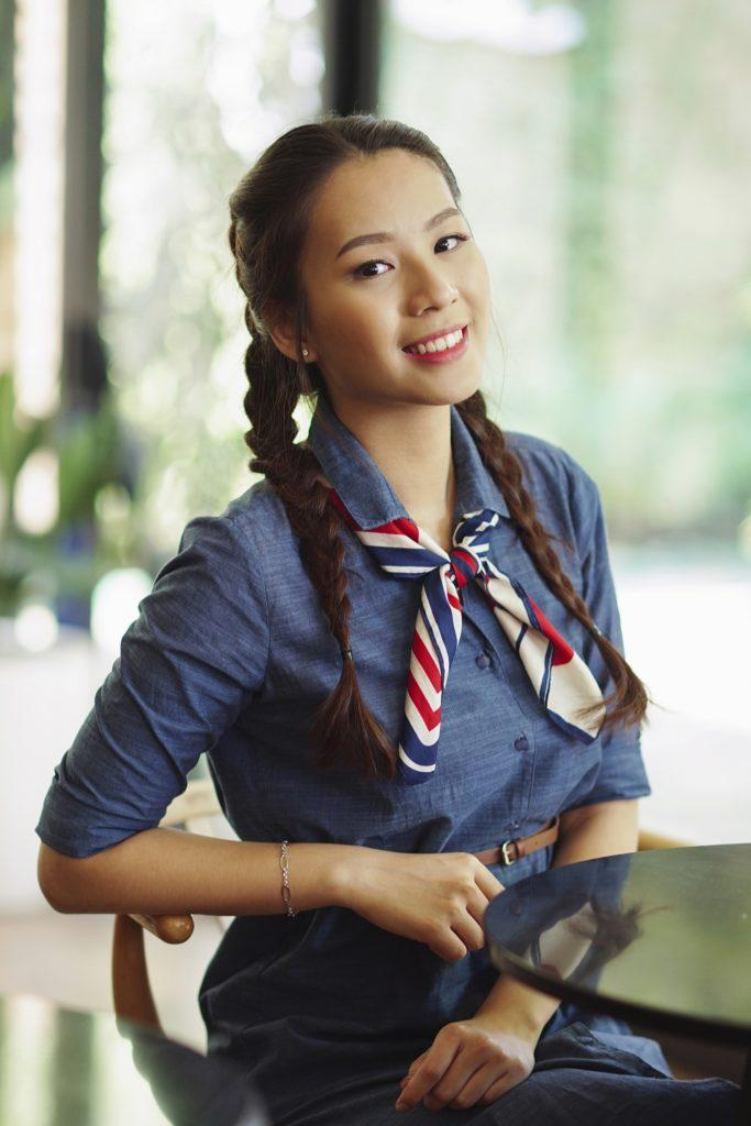 Messy side braid: Asian woman with long dark hair in messy two braids sitting in a cafe
