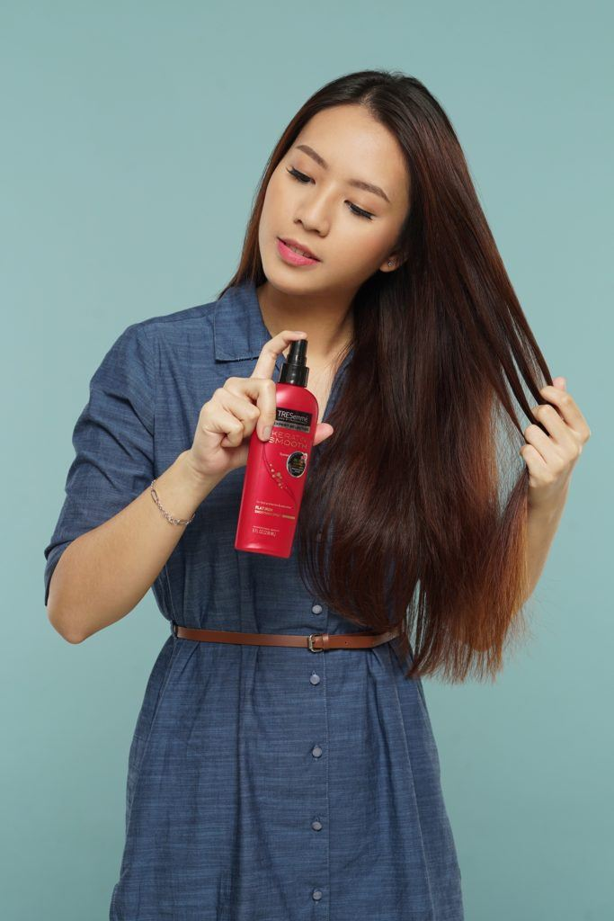 Messy two braids hairstyle: Asian woman spraying heat protectant on her long dark hair
