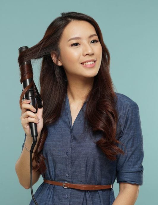 Messy two braids hairstyle: Asian woman curling her long dark hair