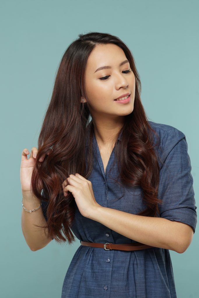 Messy two braids hairstyle: Asian woman finger-combing her long dark wavy hair