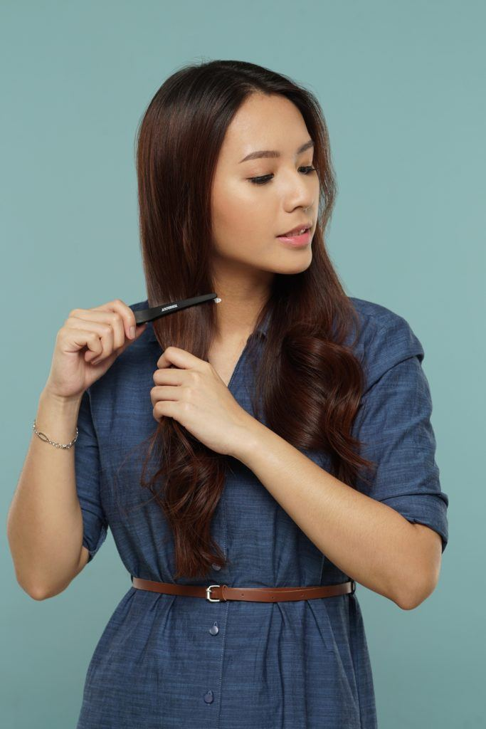 Messy two braids hairstyle: Asian woman clipping her long dark hair