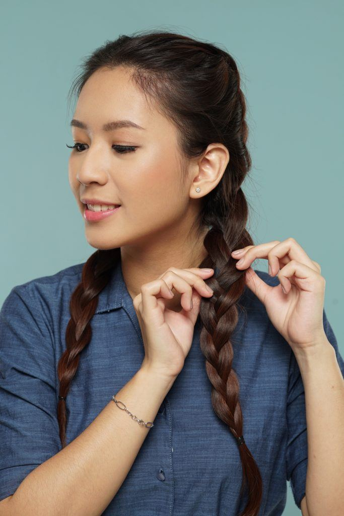 Messy two braids hairstyle: Asian woman with long dark hair in Dutch braid pulling the side of her braid