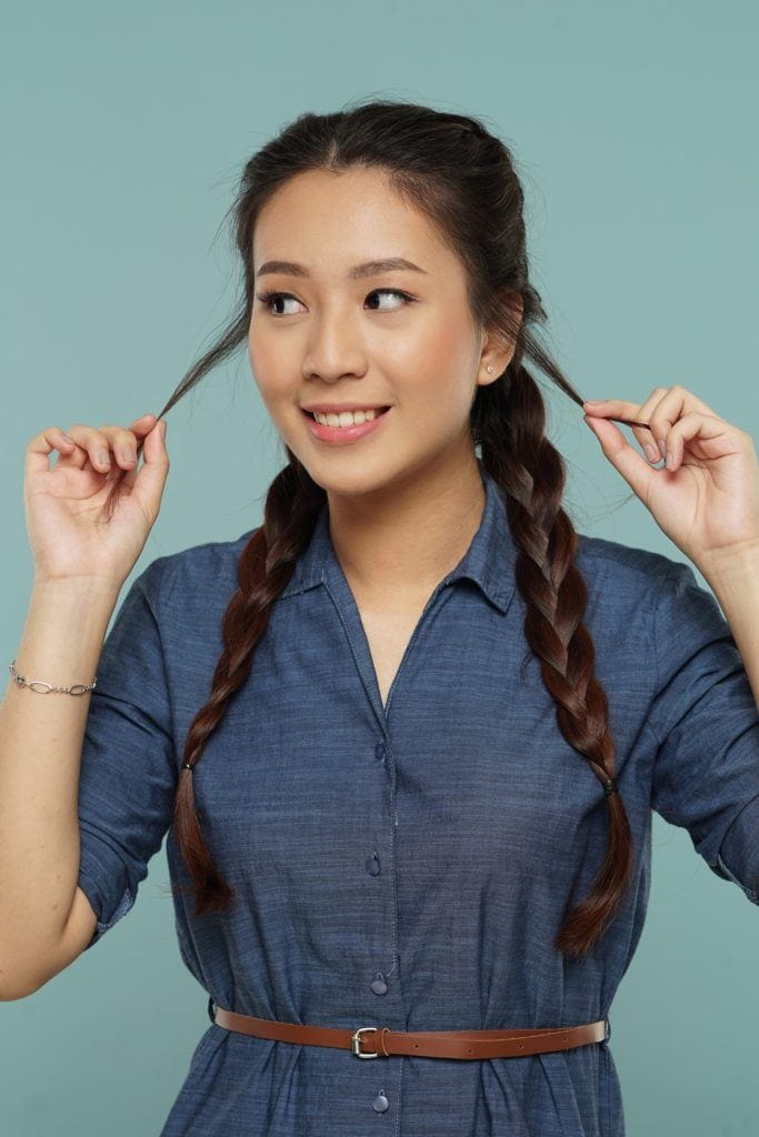 Messy side braid: asian woman wearing a denim dress, smiling with her messy two braids hairstyle