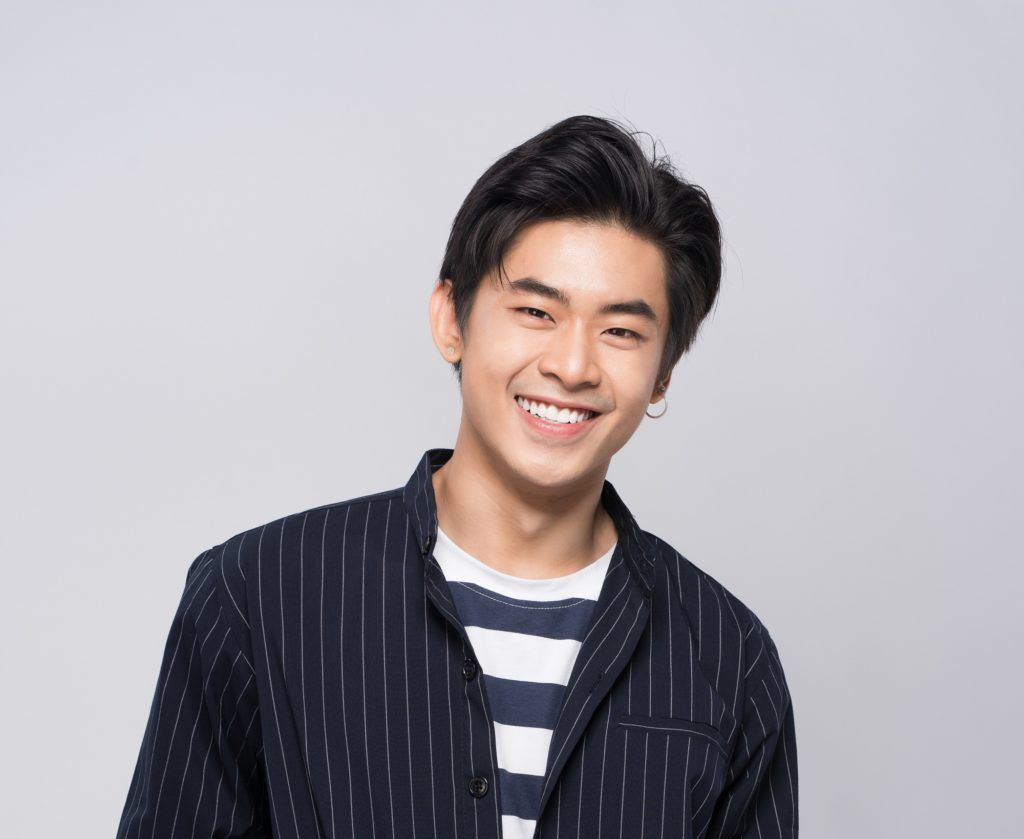 New hairstyles for men: Asian man smiling with black brushed back short hair wearing a black jacket