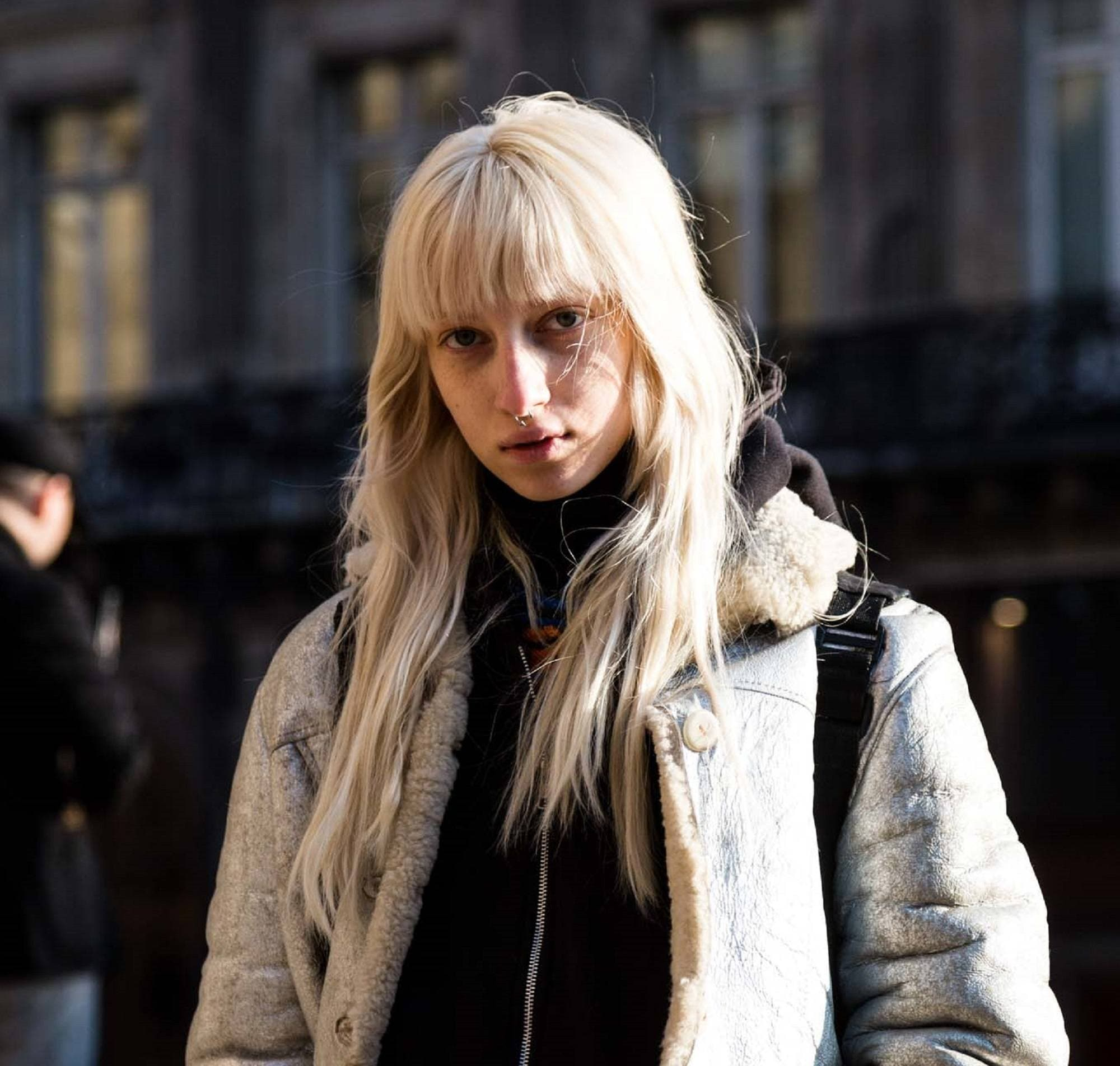 Paris Fashion Week 2019: Woman with long blonde hair with bangs wearing a jacket outdoors