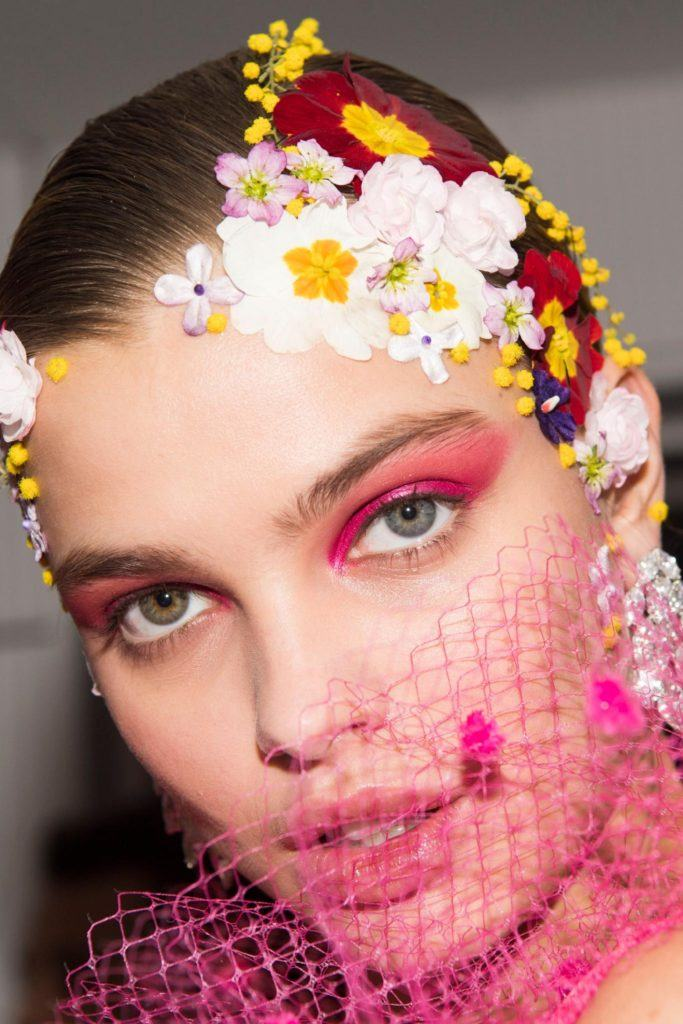 Paris Fashion Week 2019: Closeup shot of a woman with flower accessories on her hair
