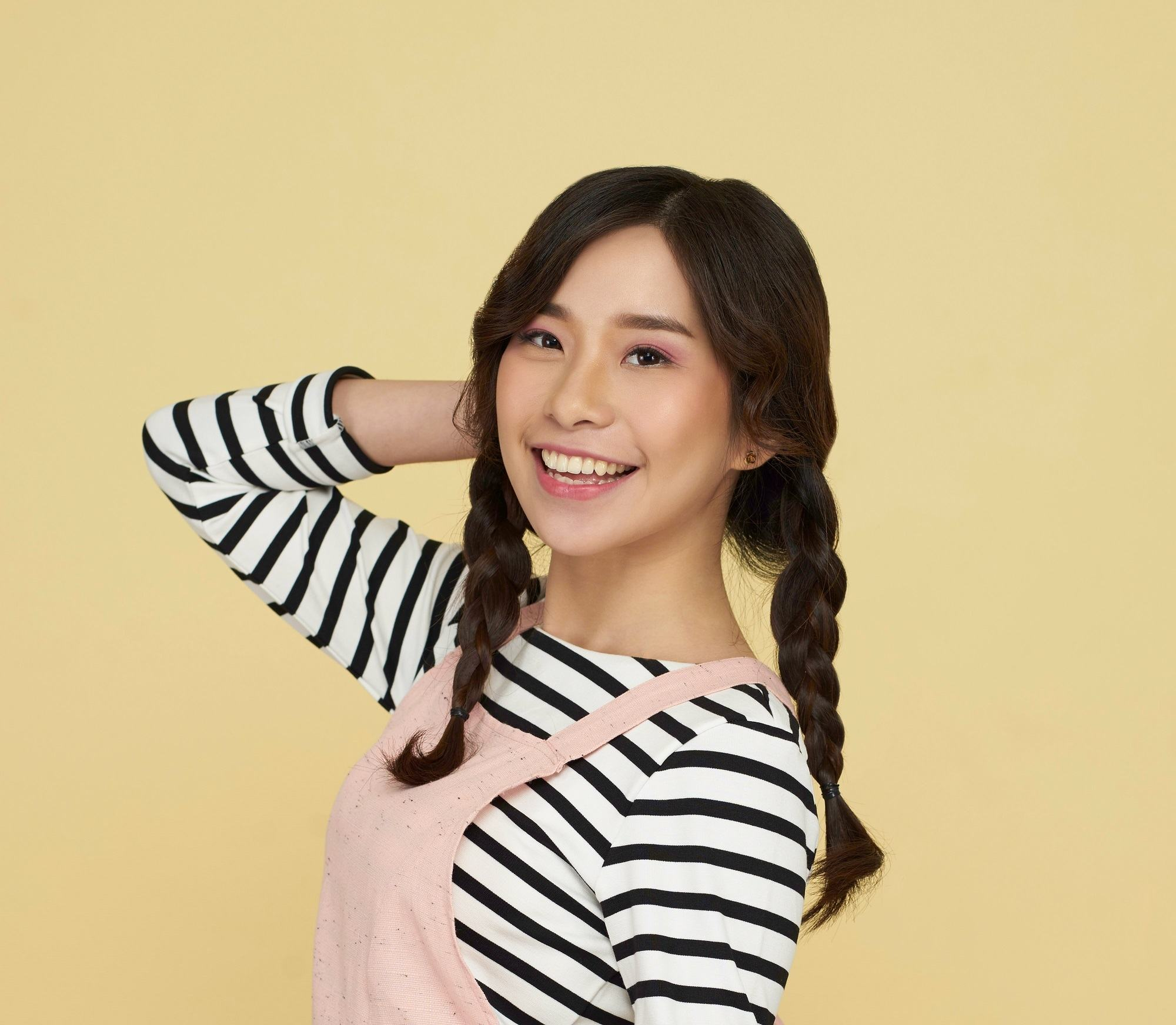 Simple braids: Asian woman wearing a pink jumper and striped long-sleeved shirt with long dark hair in twin braids