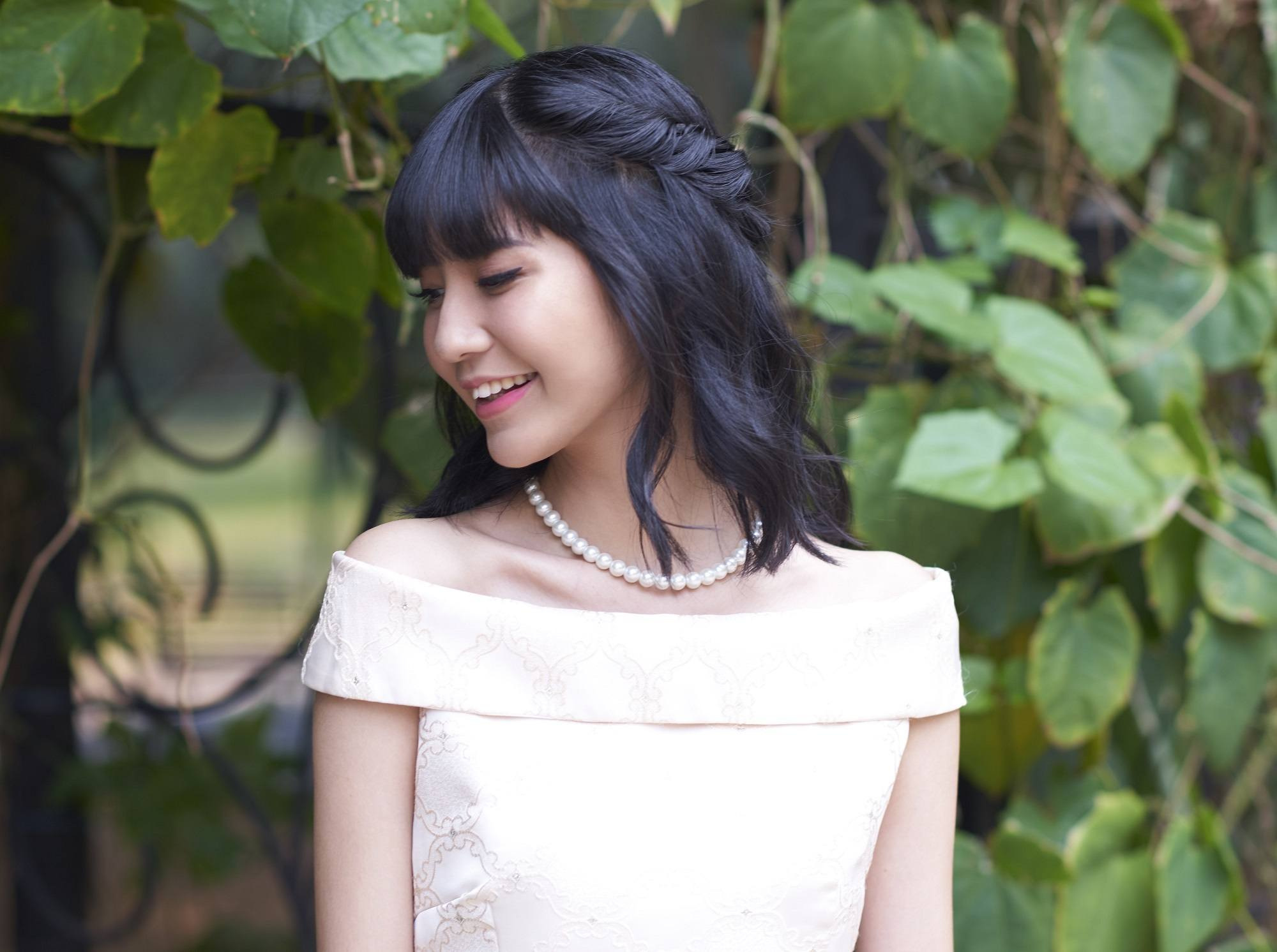 Valentine hairstyles: Asian woman wearing a peach dress with shoulder length hair in a half updo standing against a leafy gate