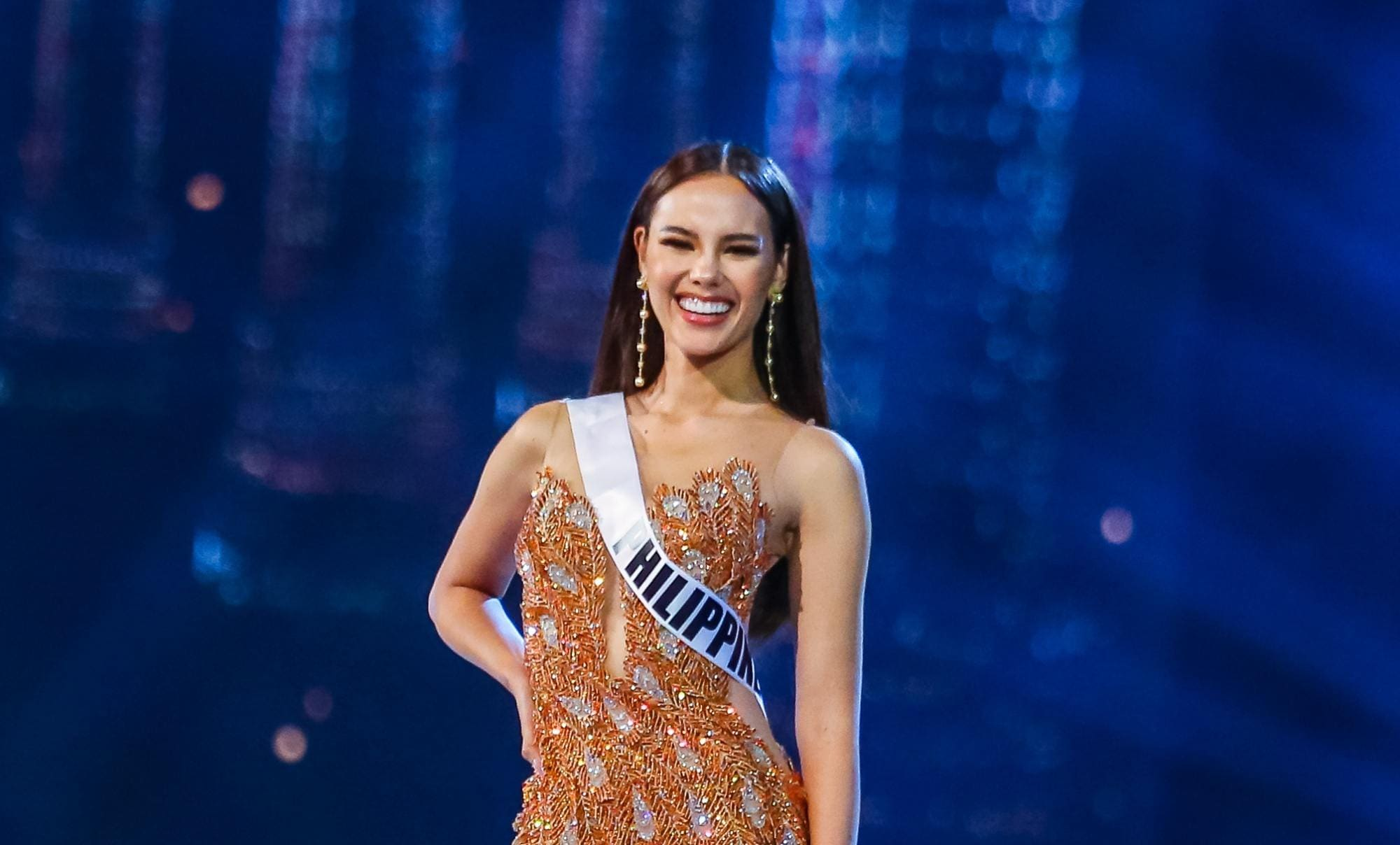 Catriona Gray: A woman with long straight black hair wearing an orange evening gown