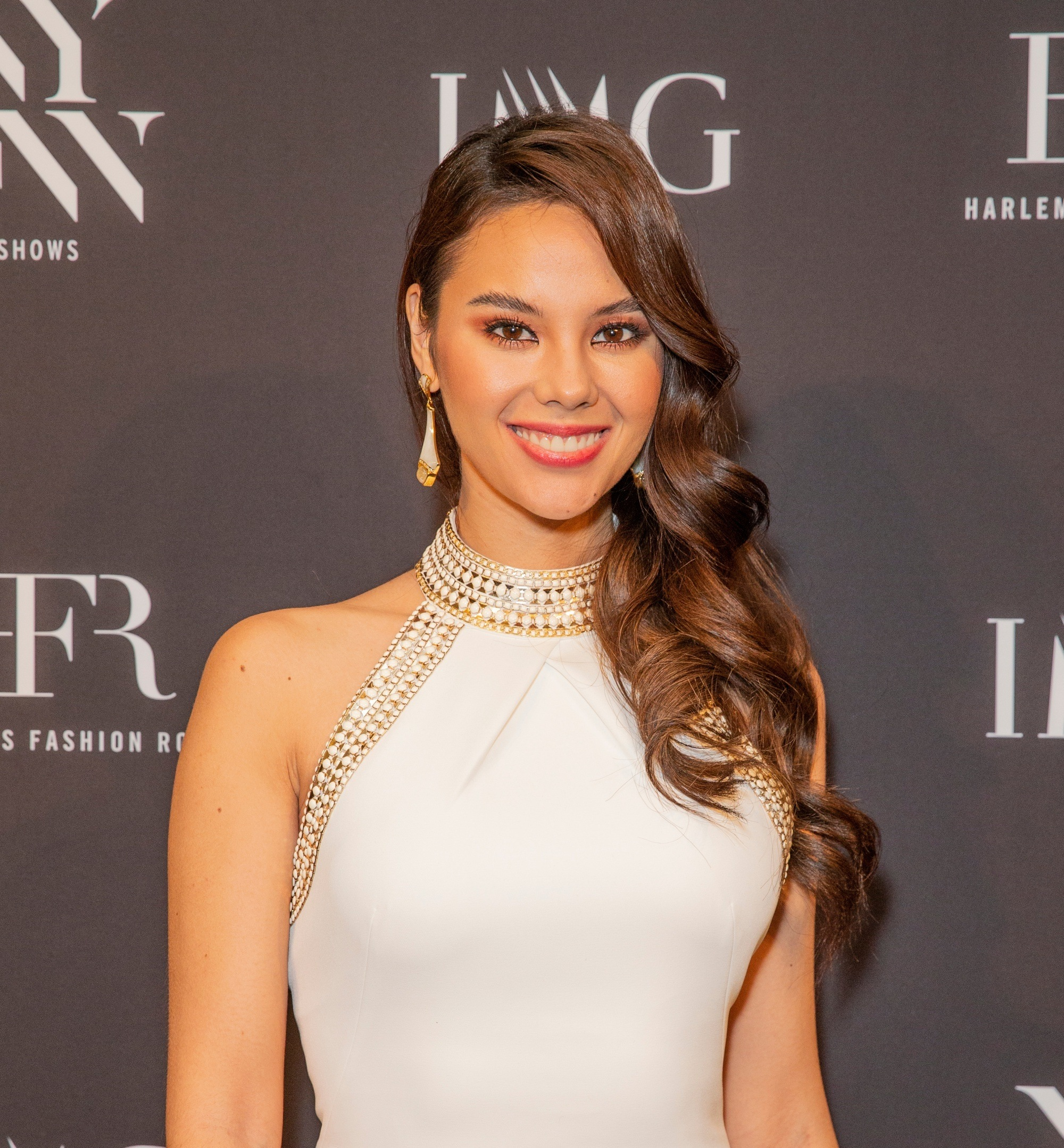 Catriona Gray wearing a white dress with long dark wavy hair