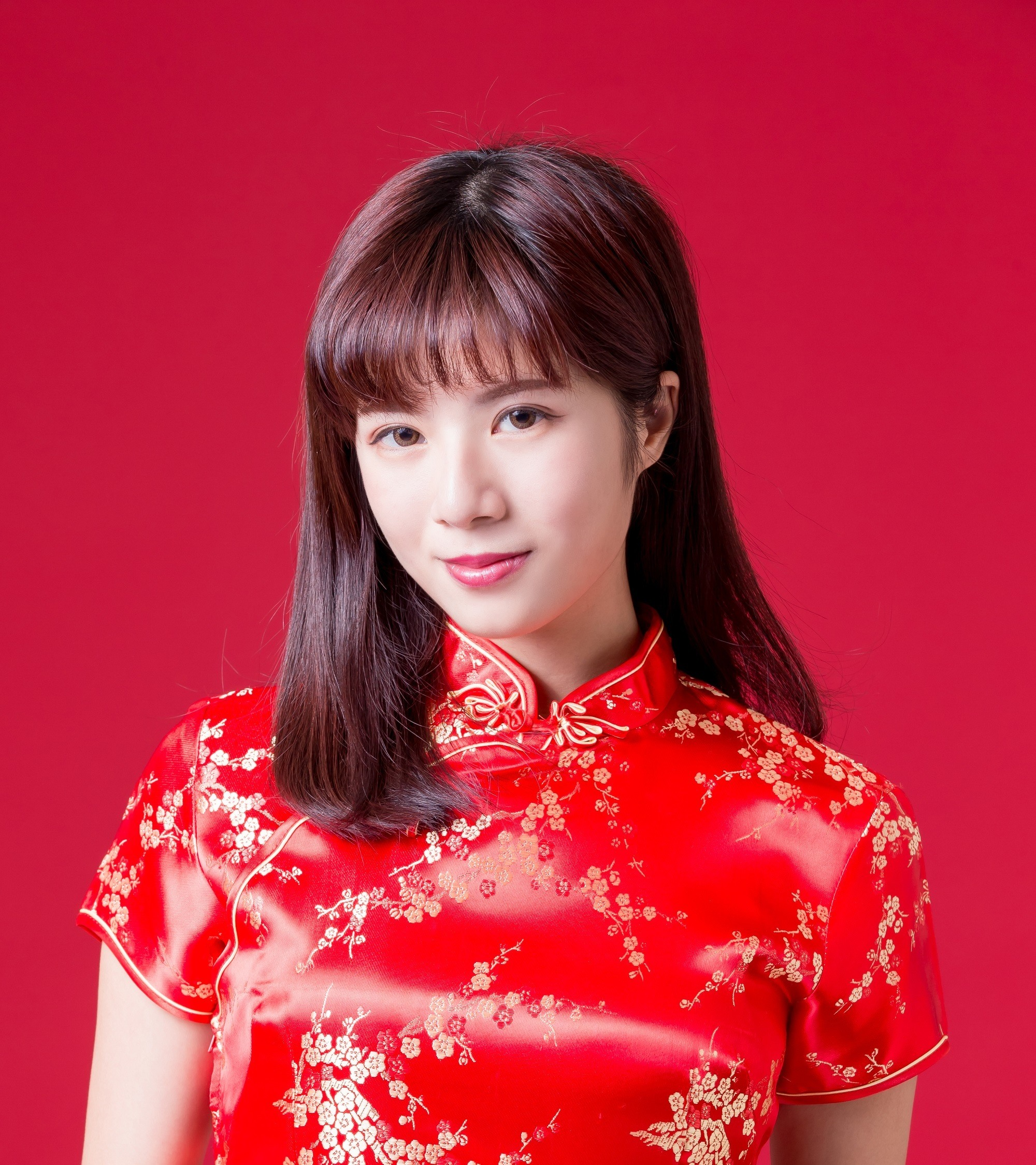 Chinese hairstyles: Closeup shot of an Asian woman with long black hair with bangs wearing a red dress