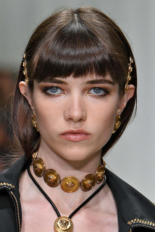 Hair clip hairstyles: Closeup shot of a woman with short dark hair with bangs wearing hair clips