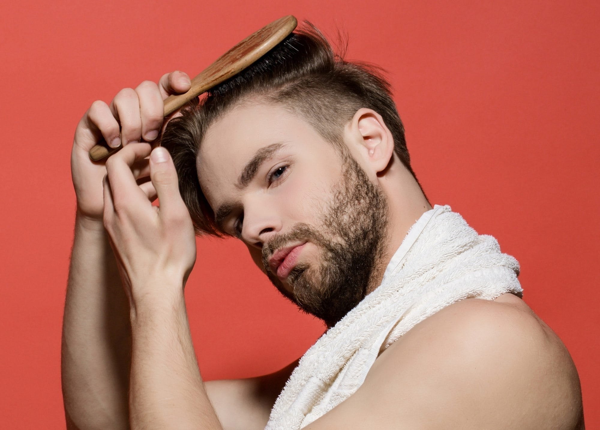 How to deep cleanse your scalp: Closeup shot of a man brushing his short hair against a red orange background