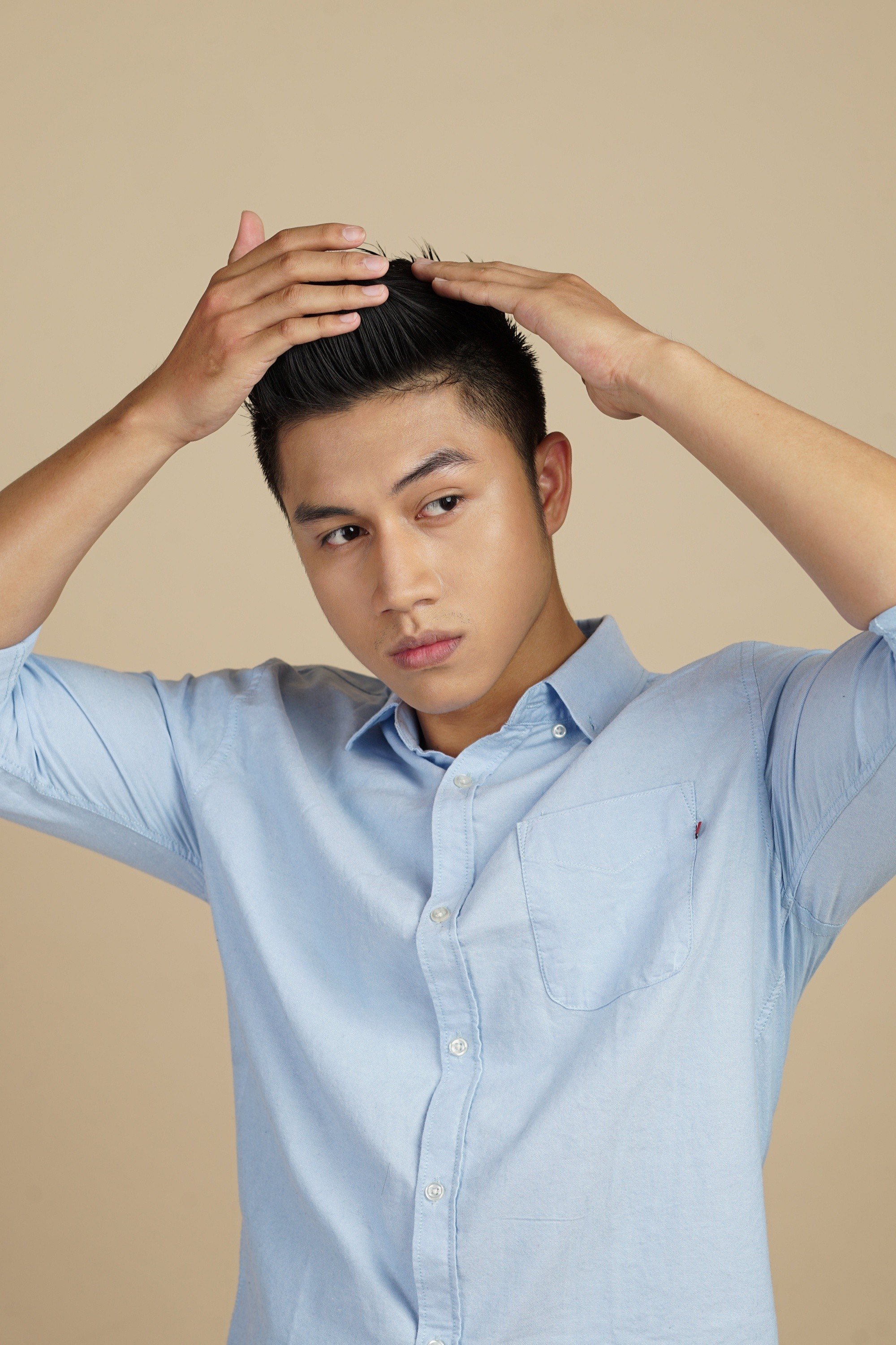 Itchy scalp: Asian man touching her short black hair and wearing a blue polo