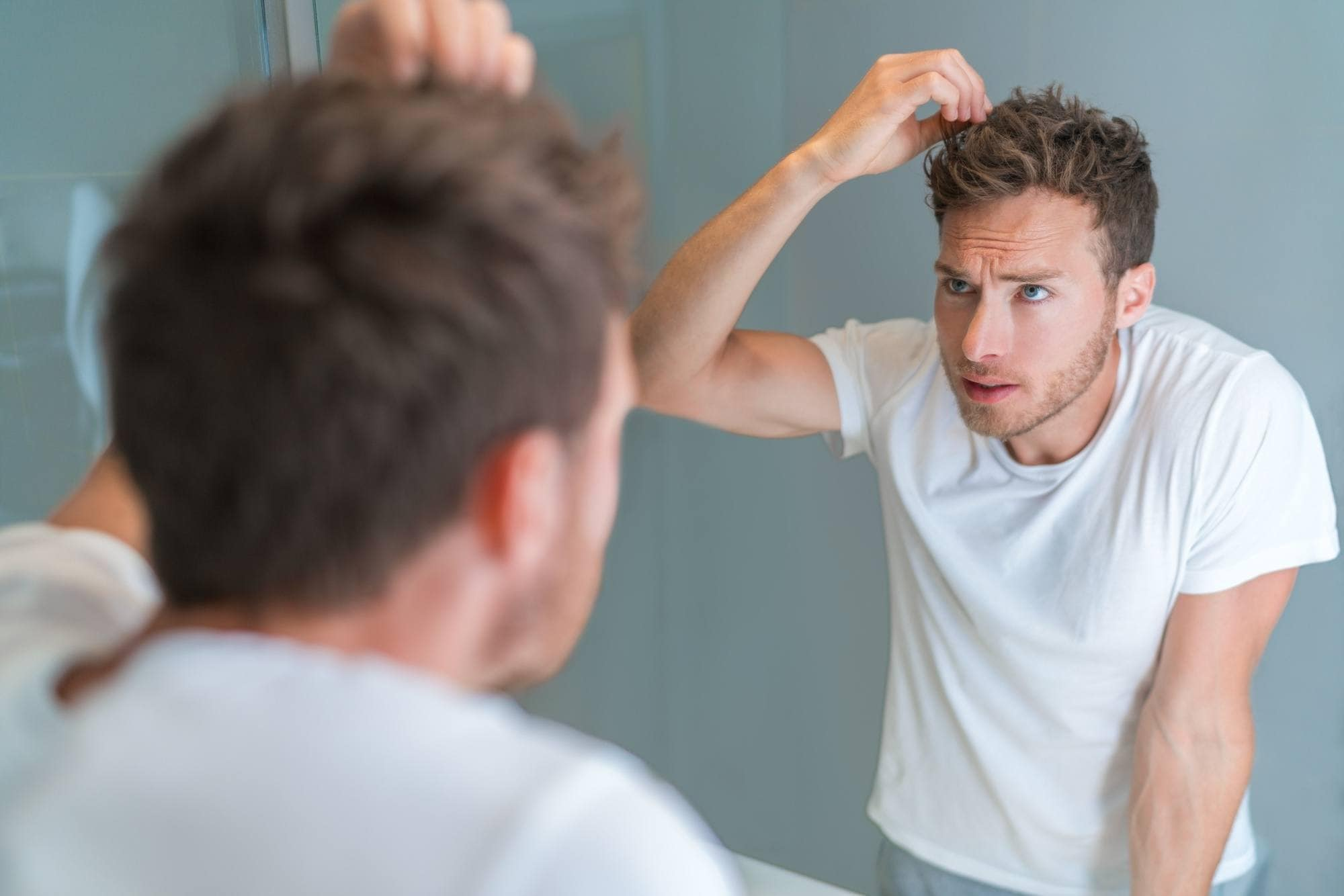 Itchy scalp: Man looking at a mirror touching her dark brown hair