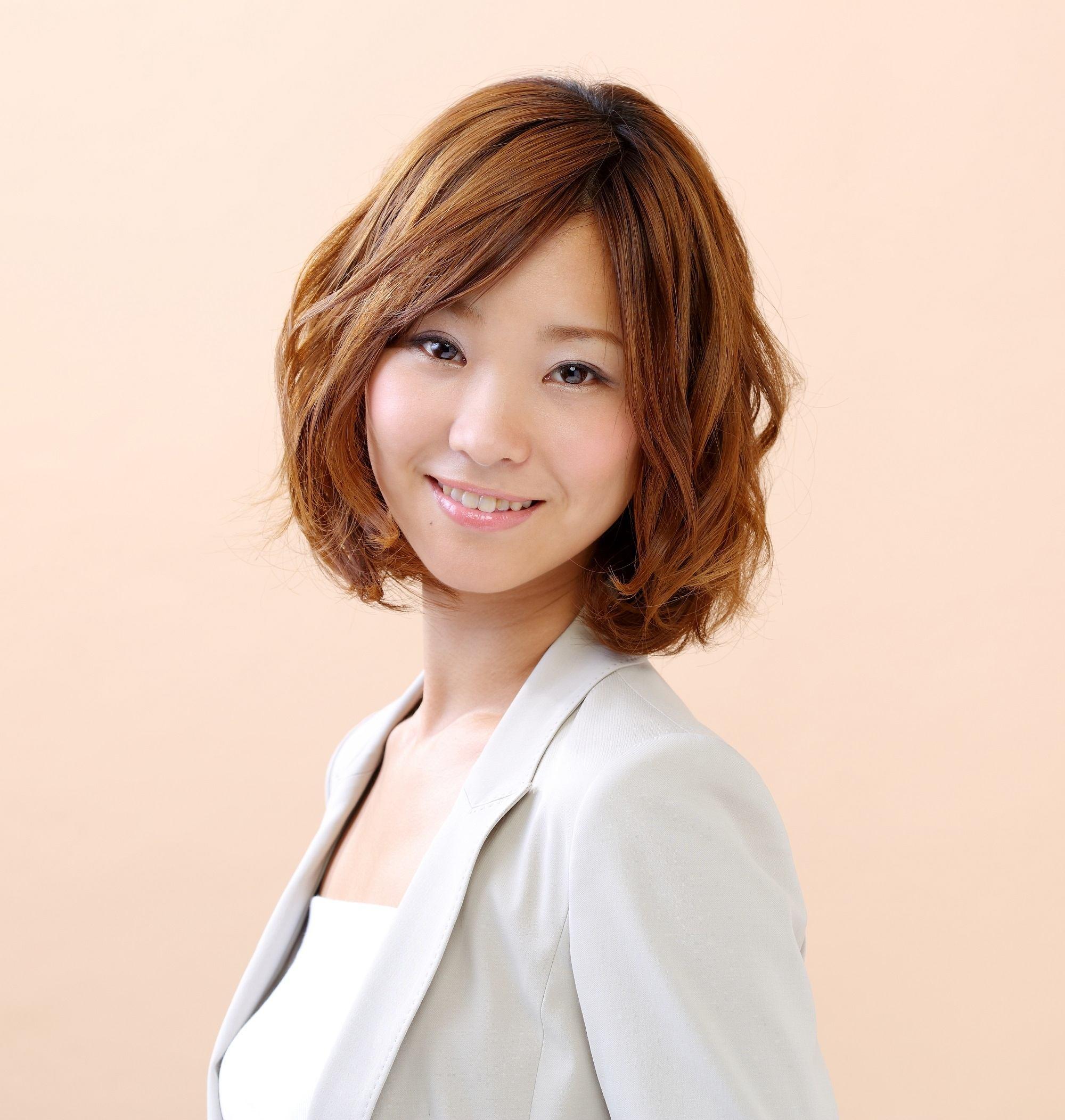Layered haircuts with bangs: Closeup shot of an Asian woman with short wavy brown hair wearing a gray blazer