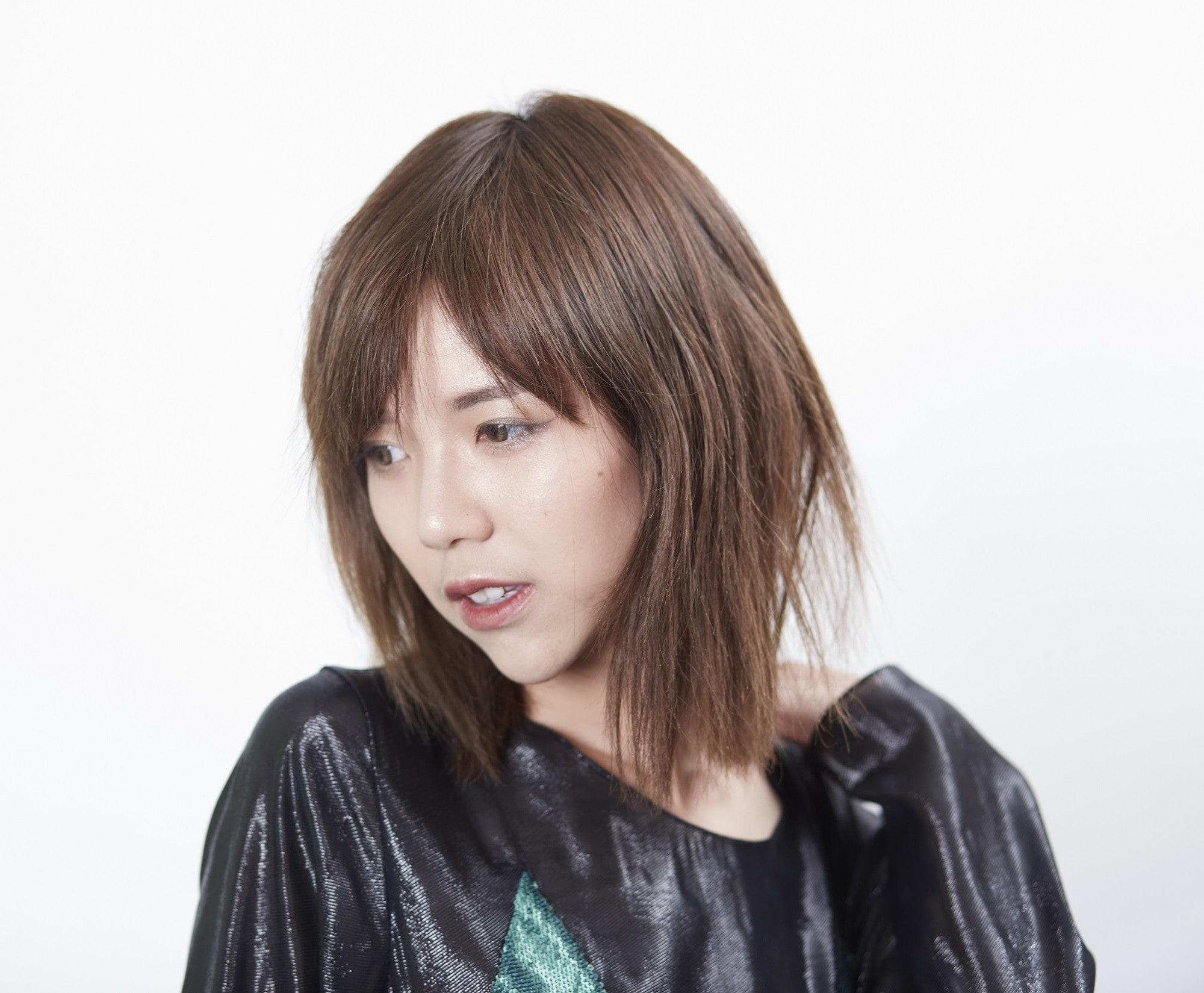 Layered haircuts with bangs: Closeup shot of an Asian woman with brown layered hair with bangs