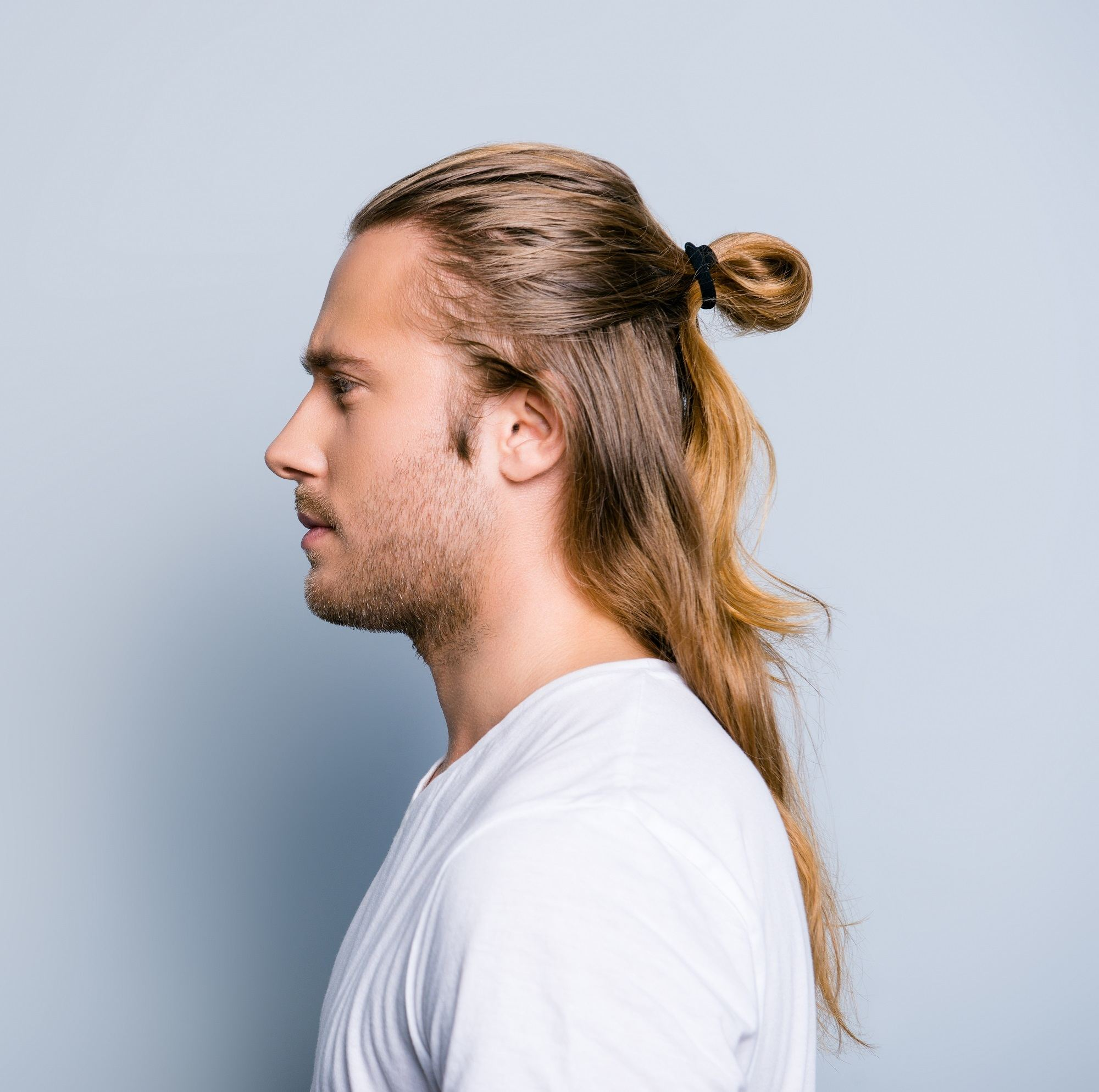 Man ponytail: Side view of a man with long brown hair in a half ponytail
