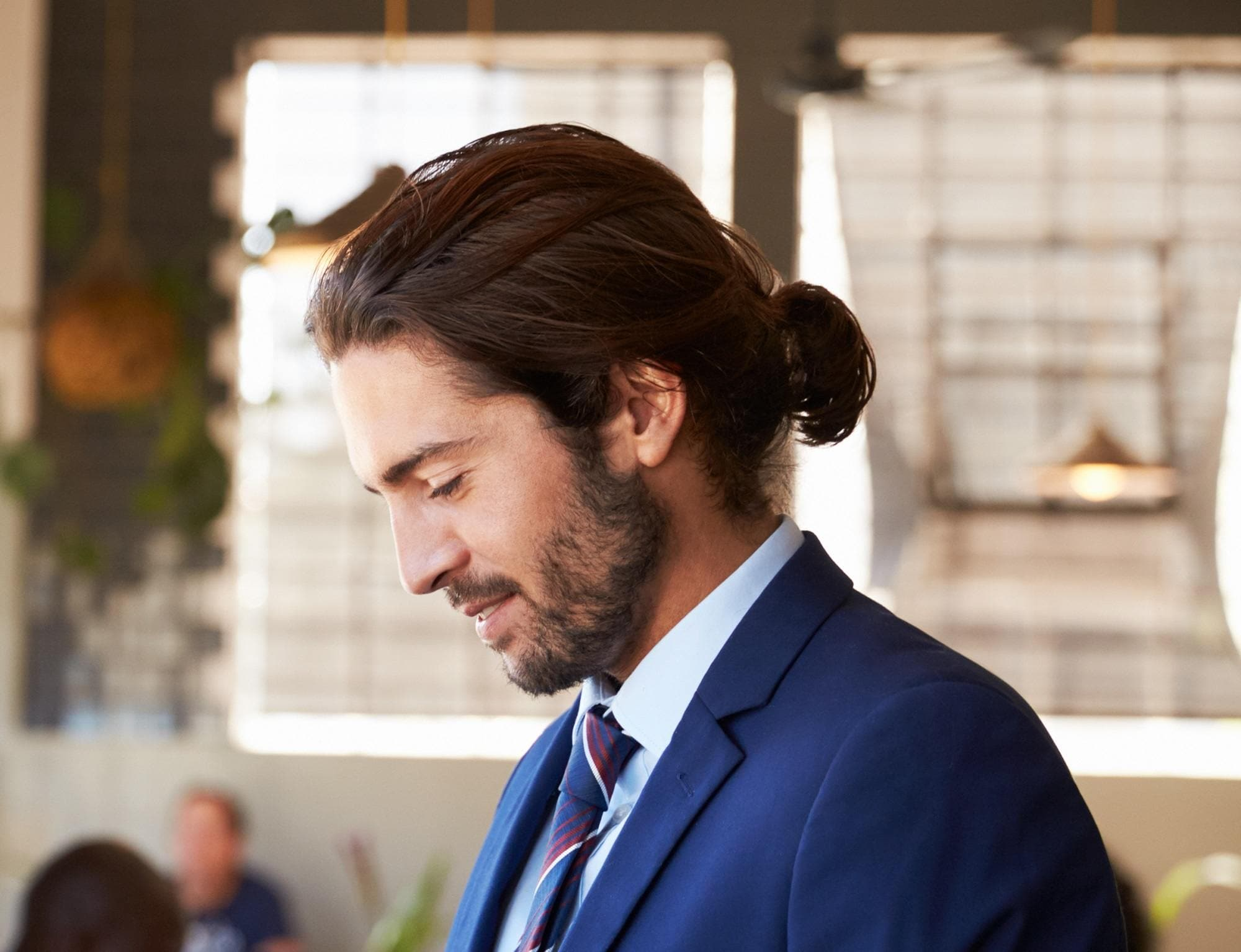 Man ponytail: Closeup side view shot of a man with brown hair in a low ponytail wearing a blue suit