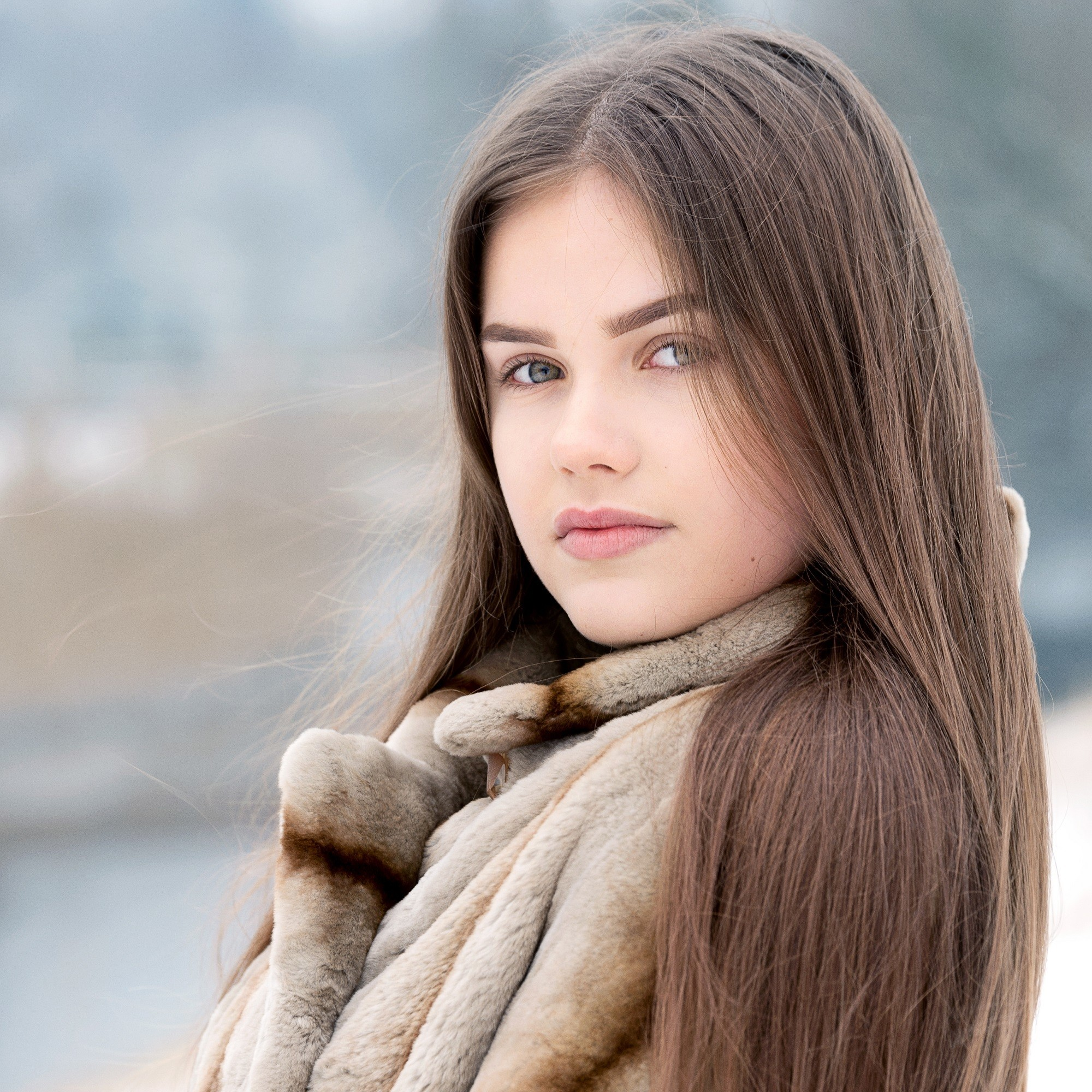 Medium brown hair color: Caucasian woman with long straight ash brown hair wearing a coat outdoors