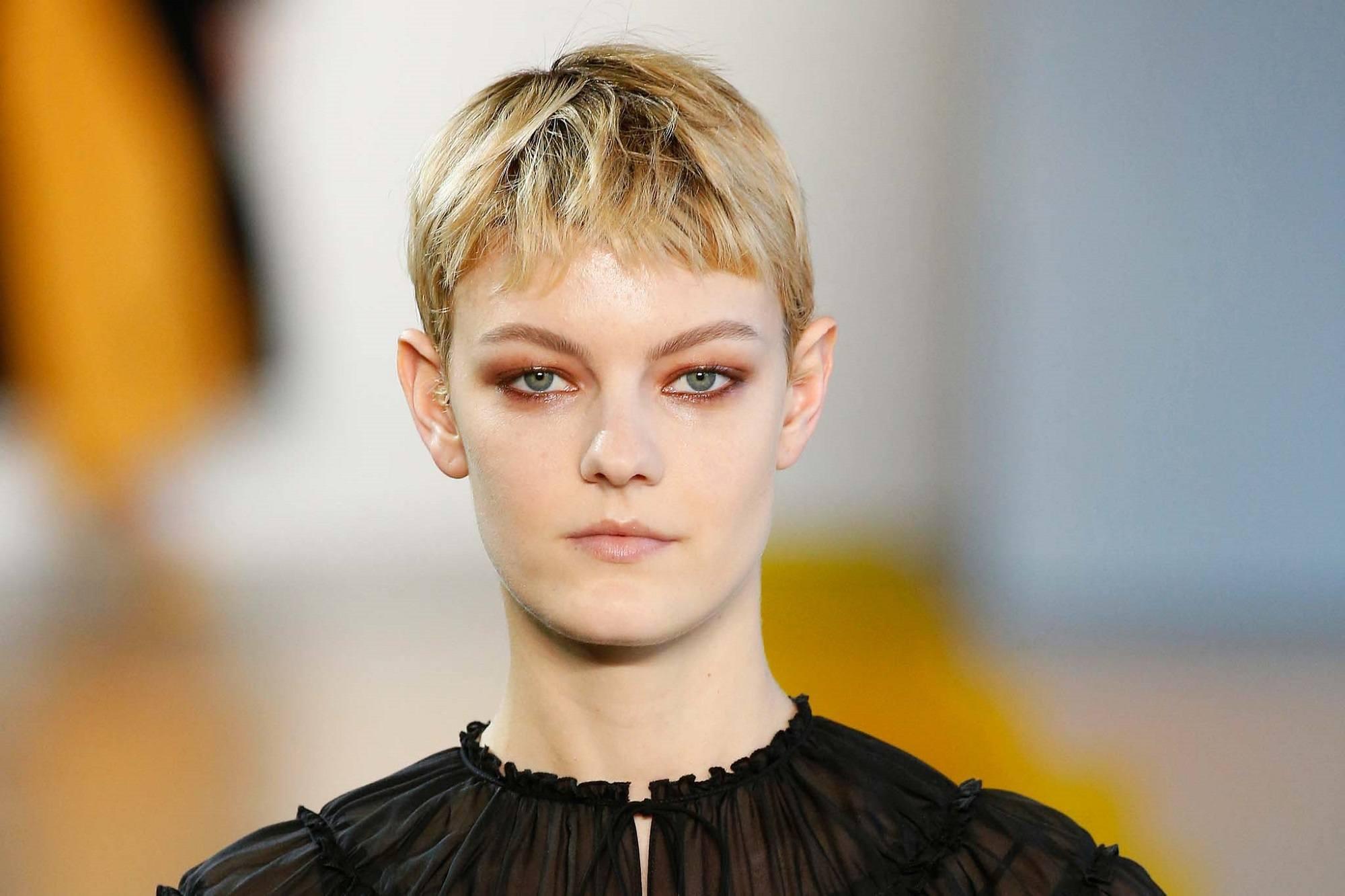 New York Fashion Week hair: Closeup shot of a woman with short blonde pixie cut wearing a black hair