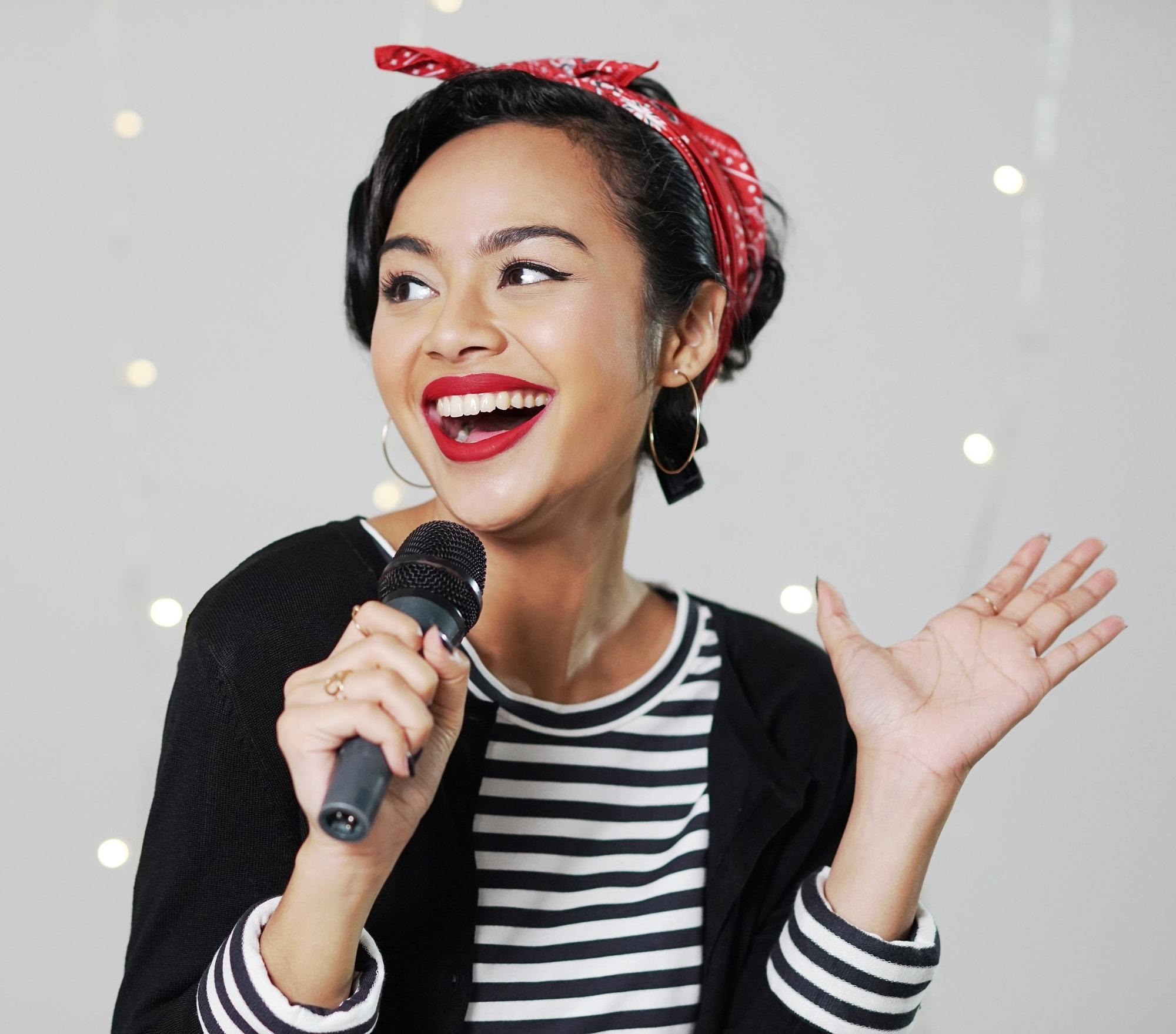Pin up hair: Closeup shot of an Asian woman with pin up hair singing with fairy lights in the background