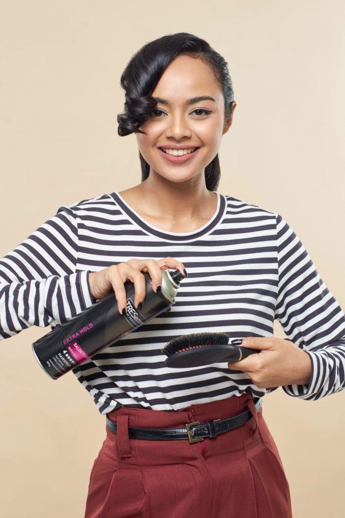 Pin up hair: Asian woman with long black hair in ponytail spraying hairspray on her brush