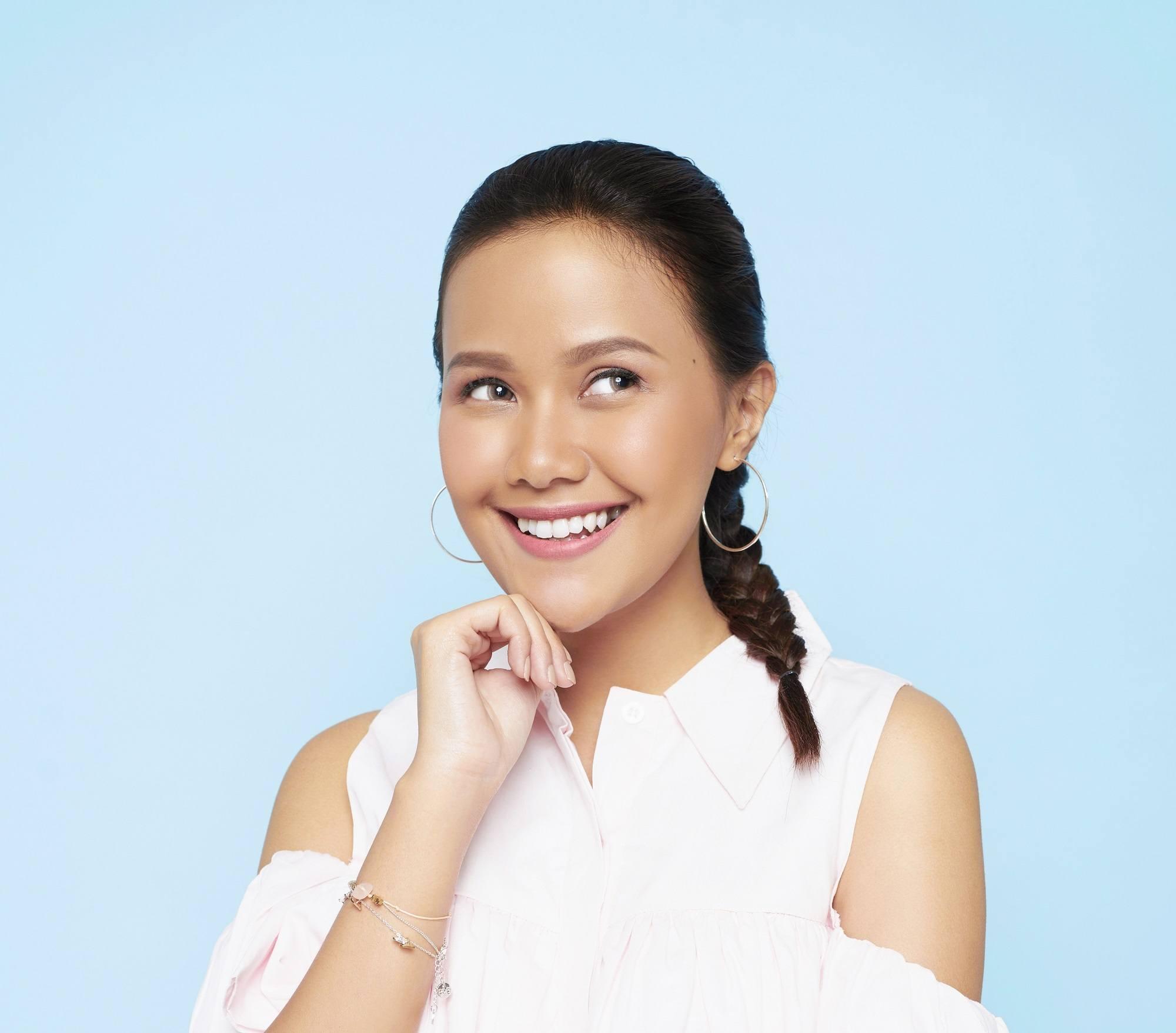 Pretty braids: Closeup shot of an Asian woman with long black hair in a Dutch braid