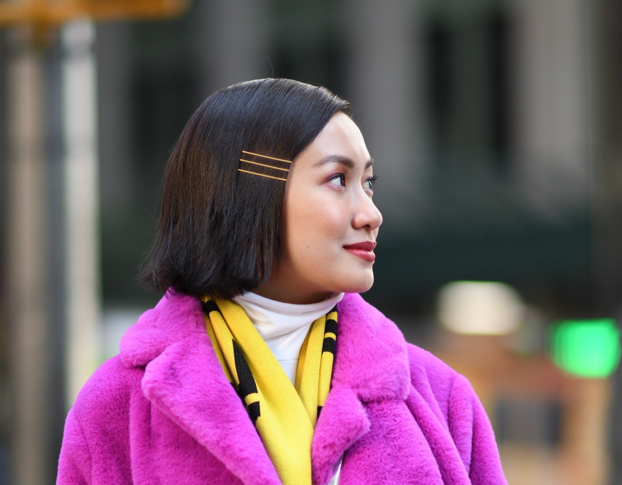Side sweep hair: Closeup shot of an Asian woman with dark straight lob wearing a pink coat outdoors