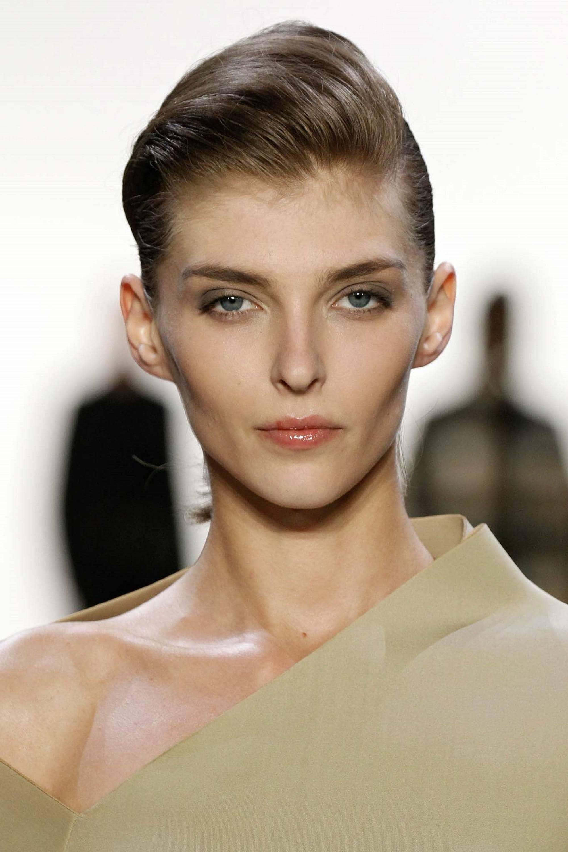 Side sweep hair: Closeup shot of a woman with dark hair in sleek pixie cut