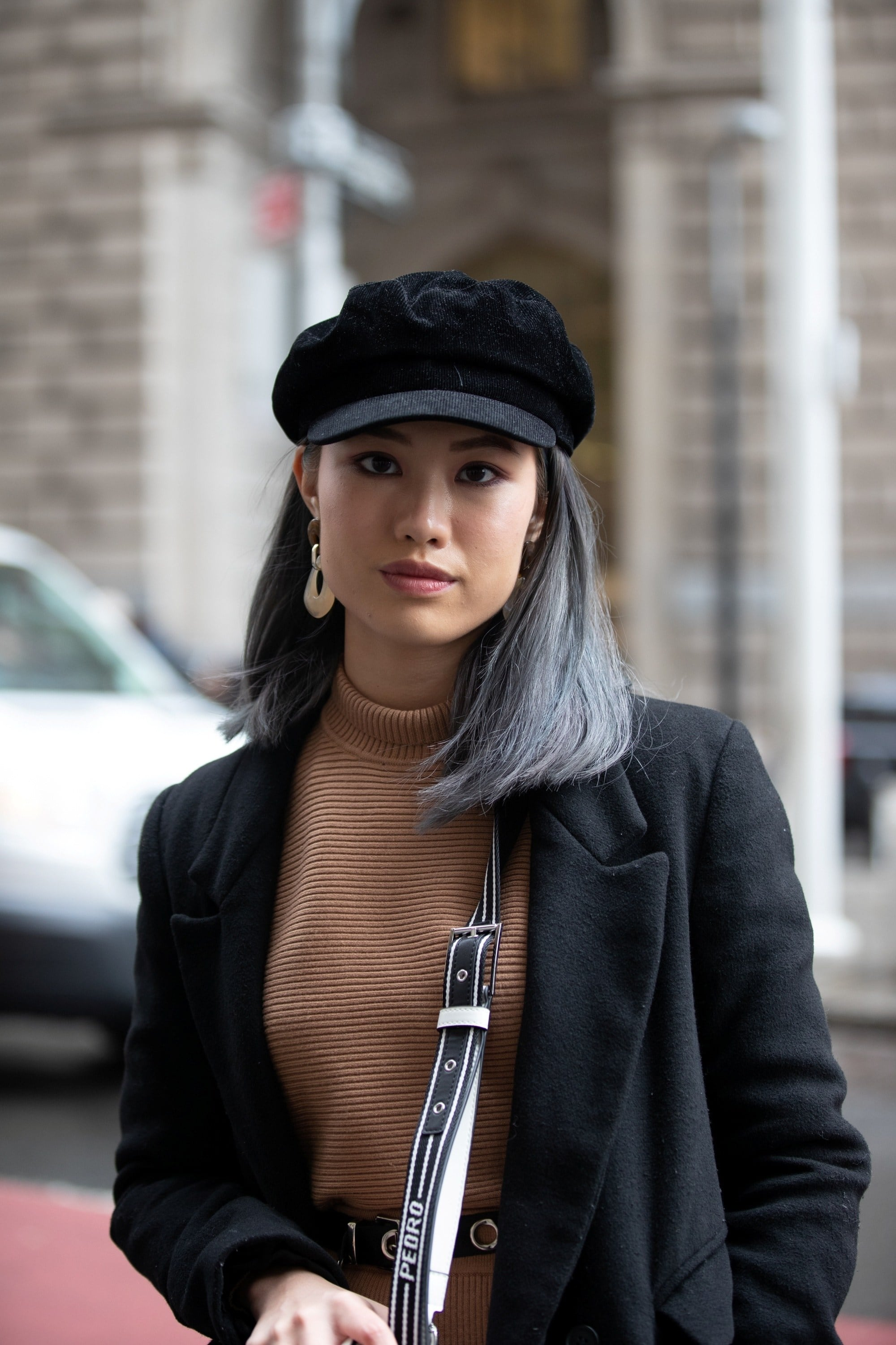 Street style hair inspiration: Woman with dip-dyed ash gray hair wearing a black hat and black jacket outdoors