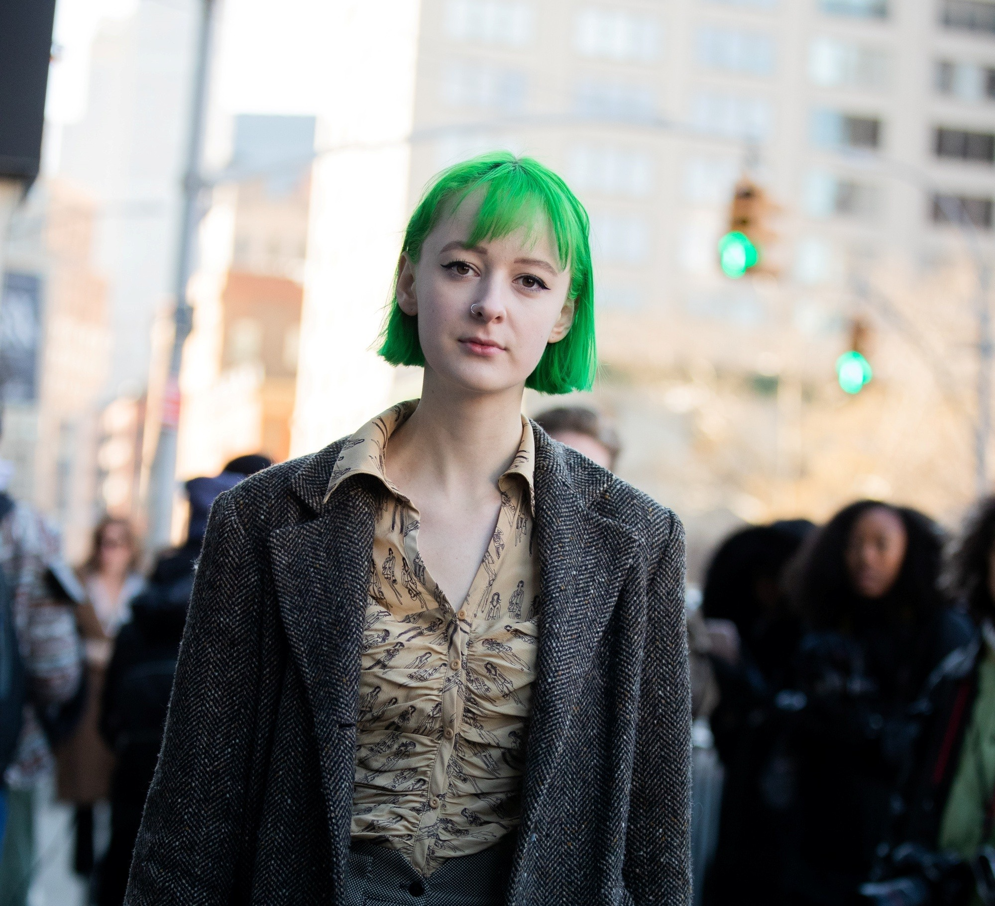 Street style hair inspiration: Woman with pale skin with a green short bob with bangs wearing dark jacket outdoors