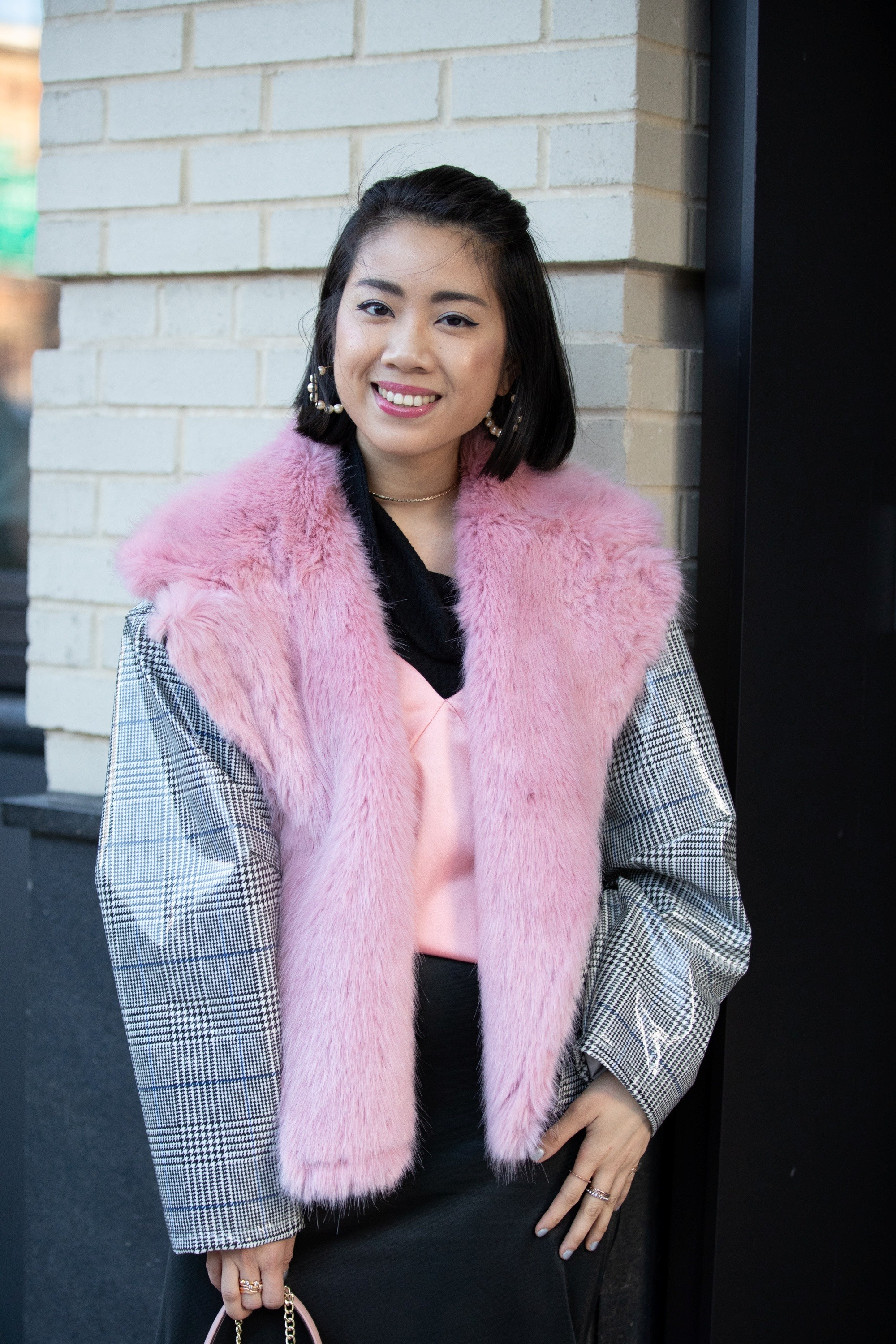 Street style hair inspiration: Asian woman with short black bob wearing a pink furry vest outdoors