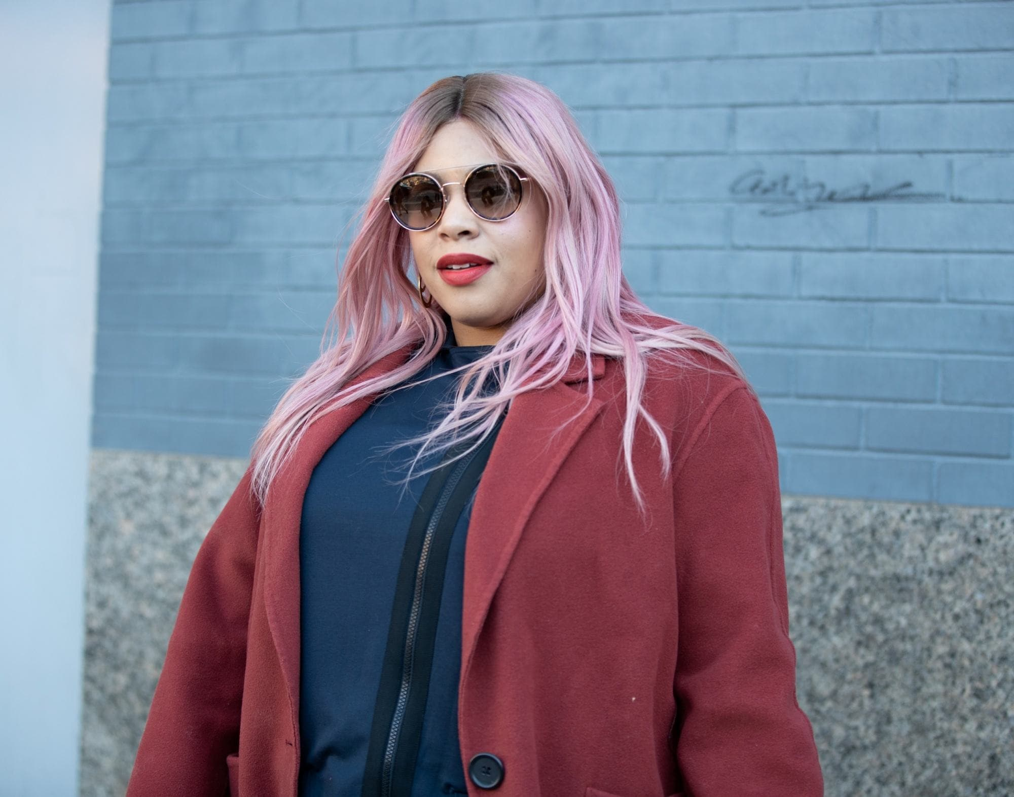 Street style hair inspiration: Woman with long pink hair wearing a red coat outdoors