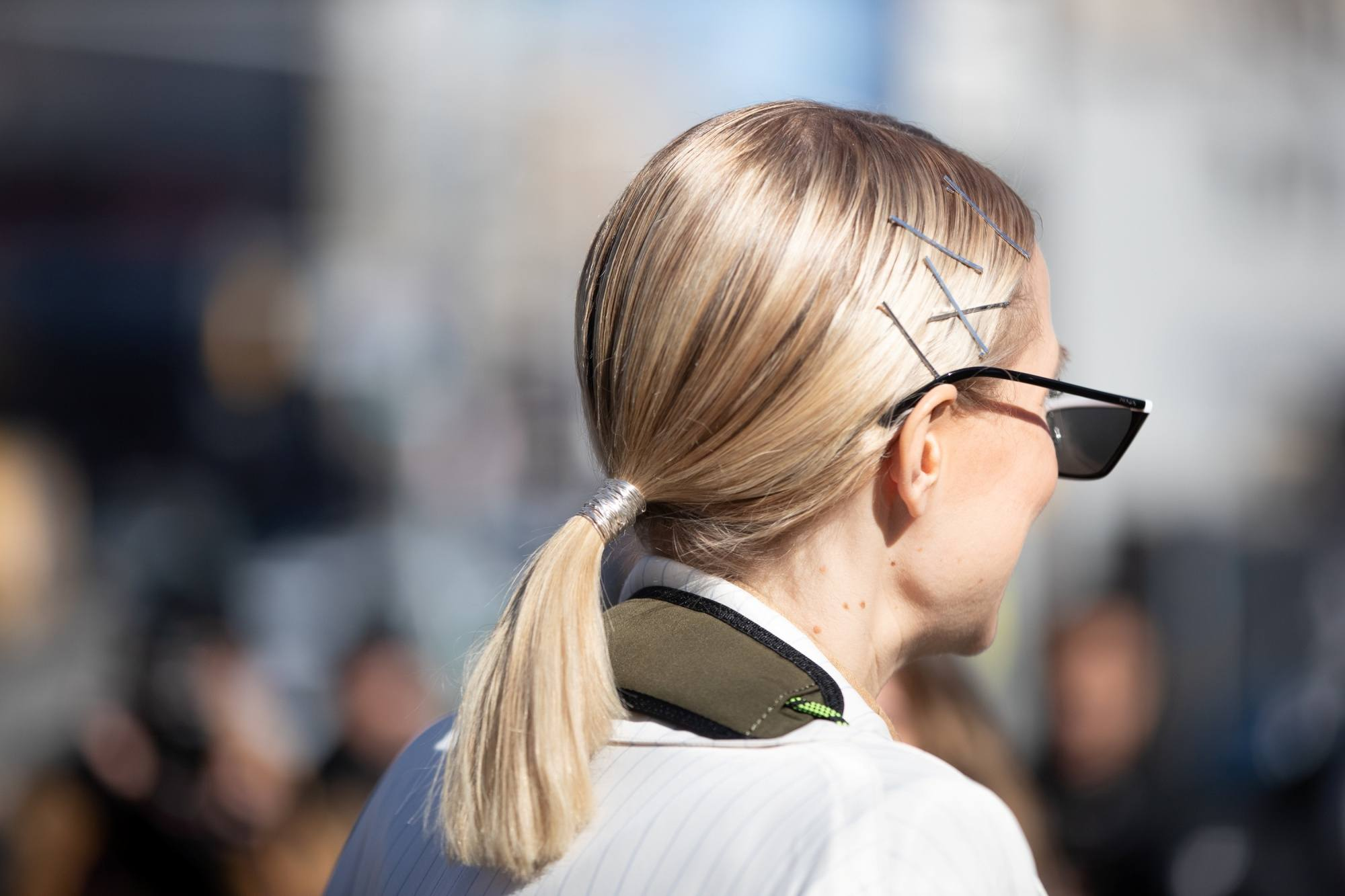 Street style hair inspiration: Back shot of a woman with shoulder length blonde hair in a ponytail outdoors