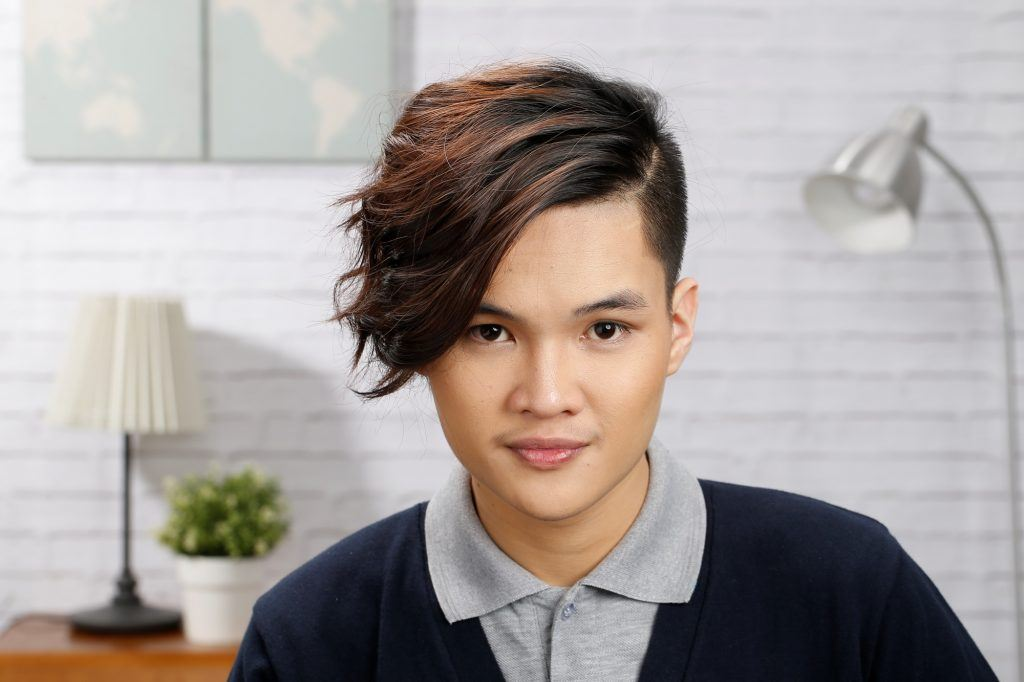 Asian man with a messy hairstyle wearing a collared shirt and cardigan