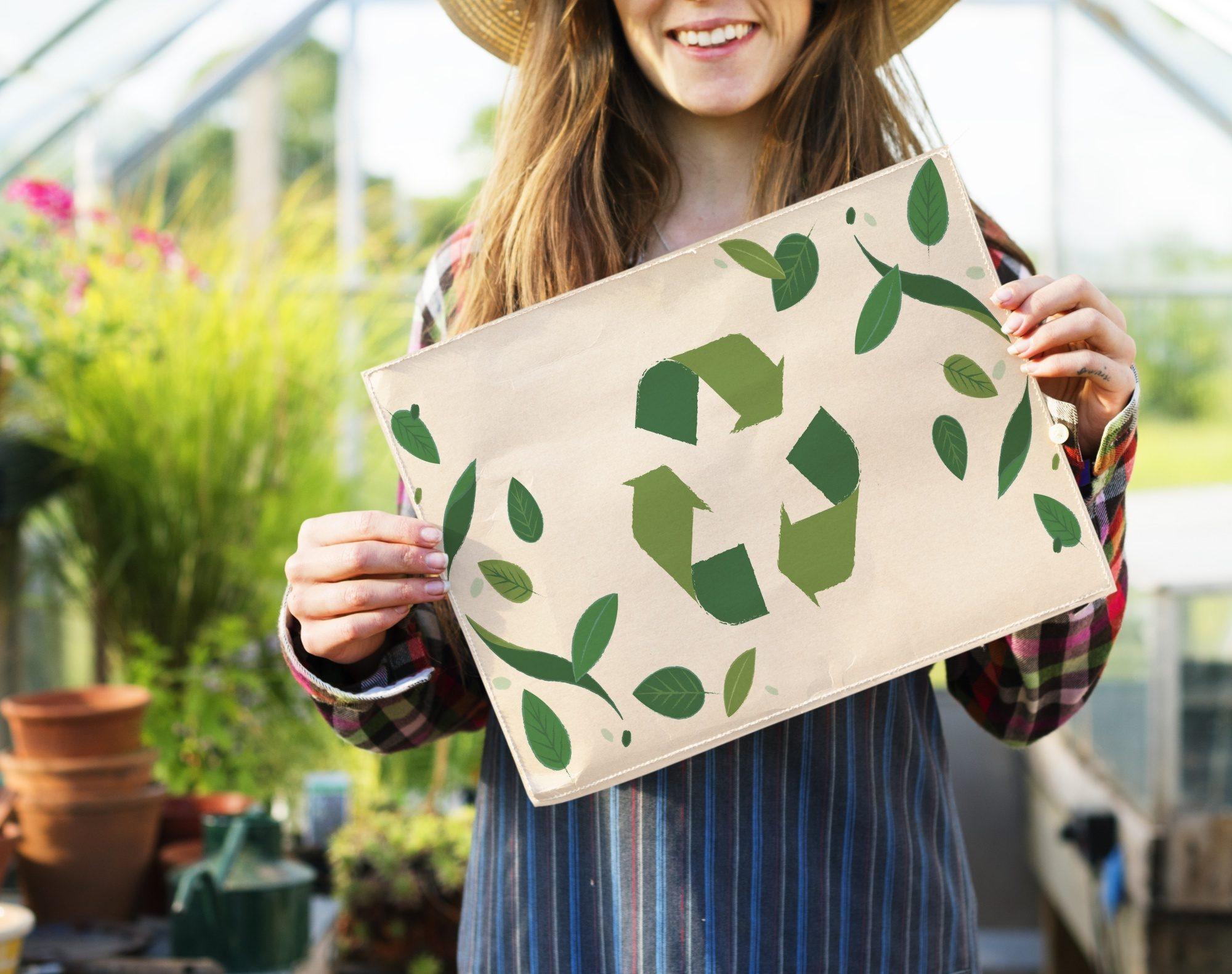All Things Hair Refillery: Woman holding a recycle sign in a greenhouse