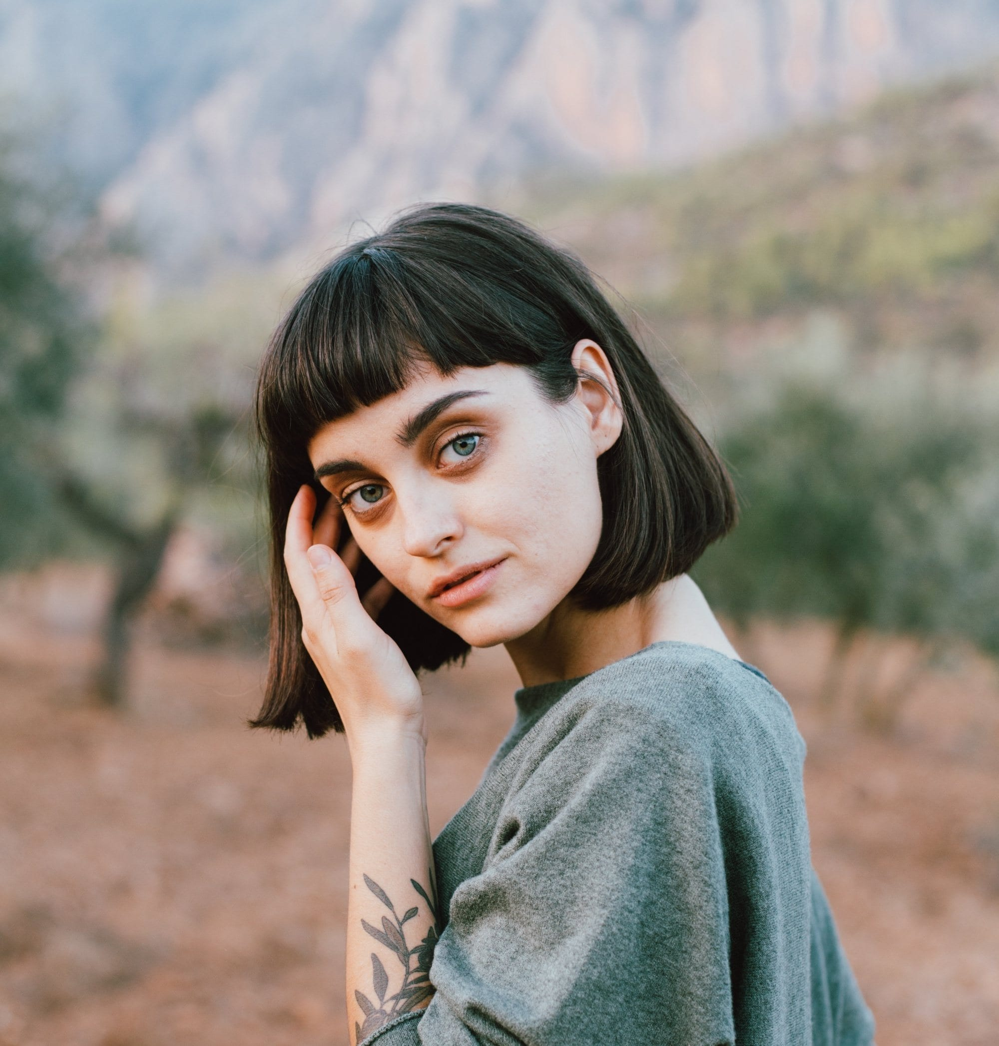 Baby bangs for short hair: Closeup shot of a woman with short black hair with baby bangs wearing a shirt in the woods