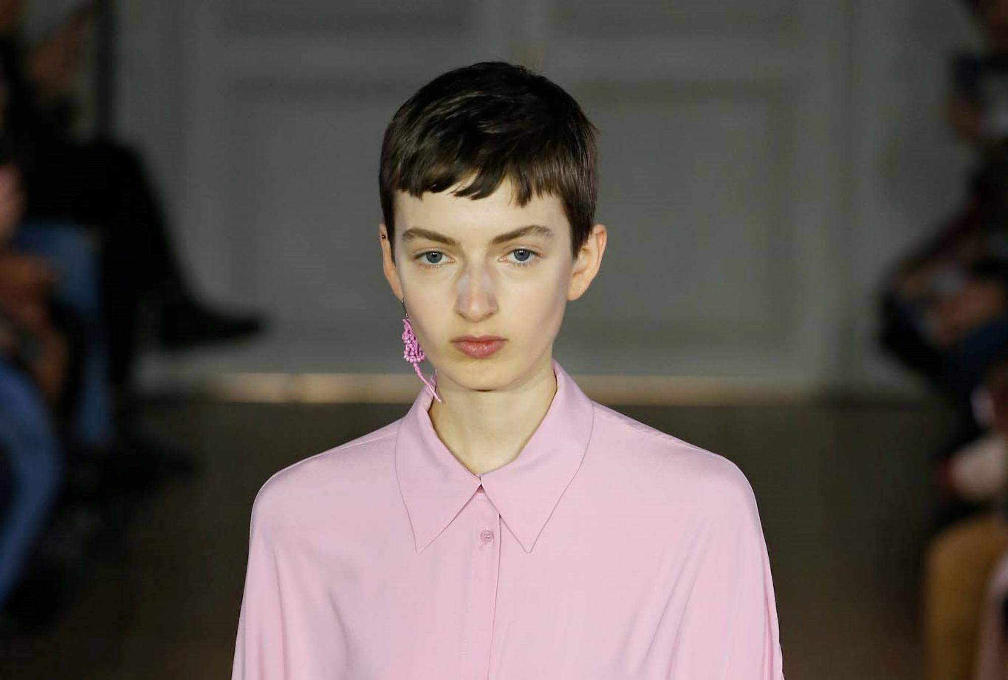 Baby bangs for short hair: Closeup shot of a woman with short dark hair in pixie cut with baby bangs wearing a pink top