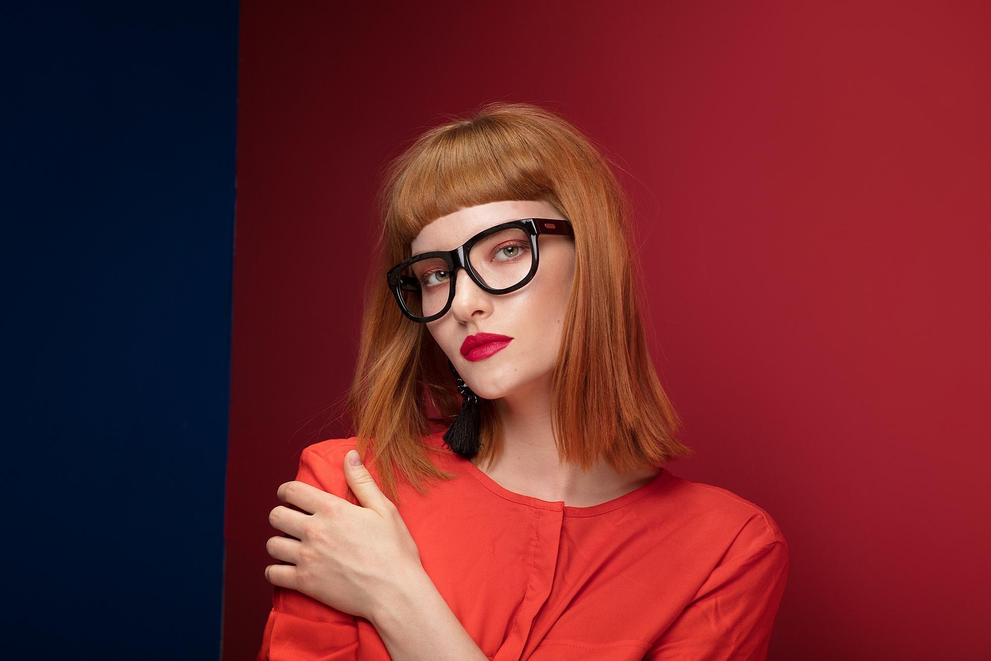 Baby bangs for short hair: Closeup shot of a woman with reddish lob with baby bangs wearing eyeglasses