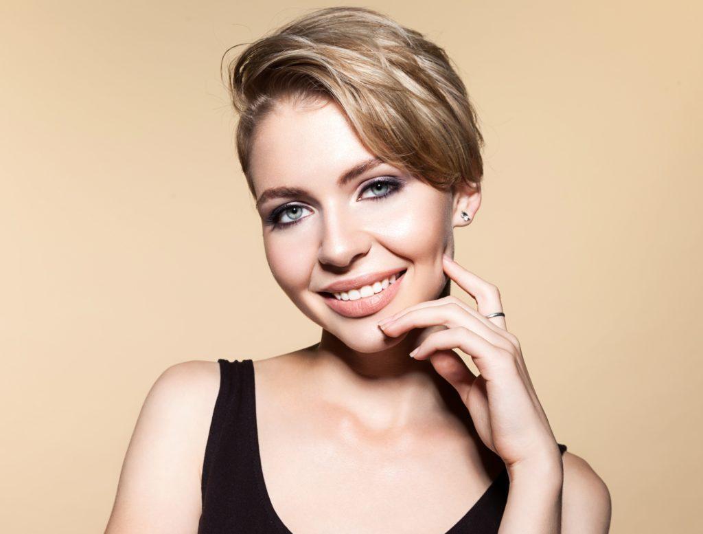 Boyish haircuts: Closeup shot of a woman with dark blonde pixie cut wearing a black tank top